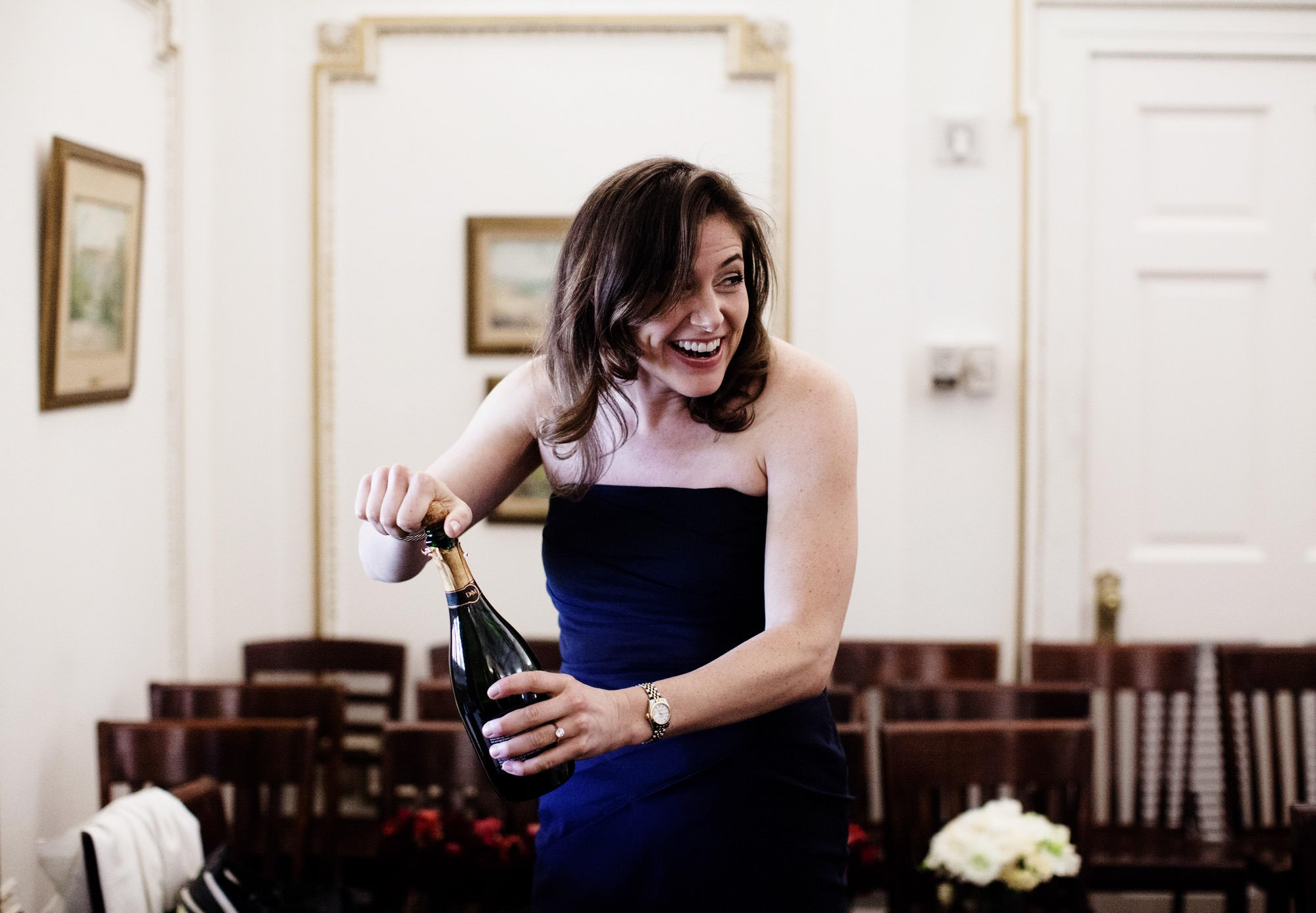 A bridesmaid opens a bottle of champaign before the DAR Memorial Continental Hall Wedding ceremony.