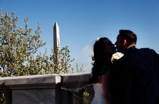 DAR Memorial Continental Hall Wedding I The bride and groom kiss with the Washington Monument in the background.