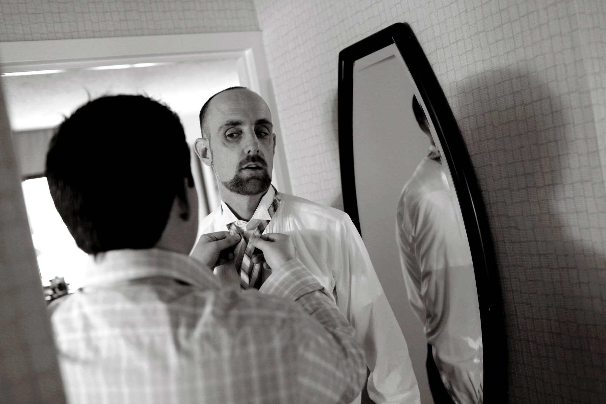 A groomsman puts on his tie.