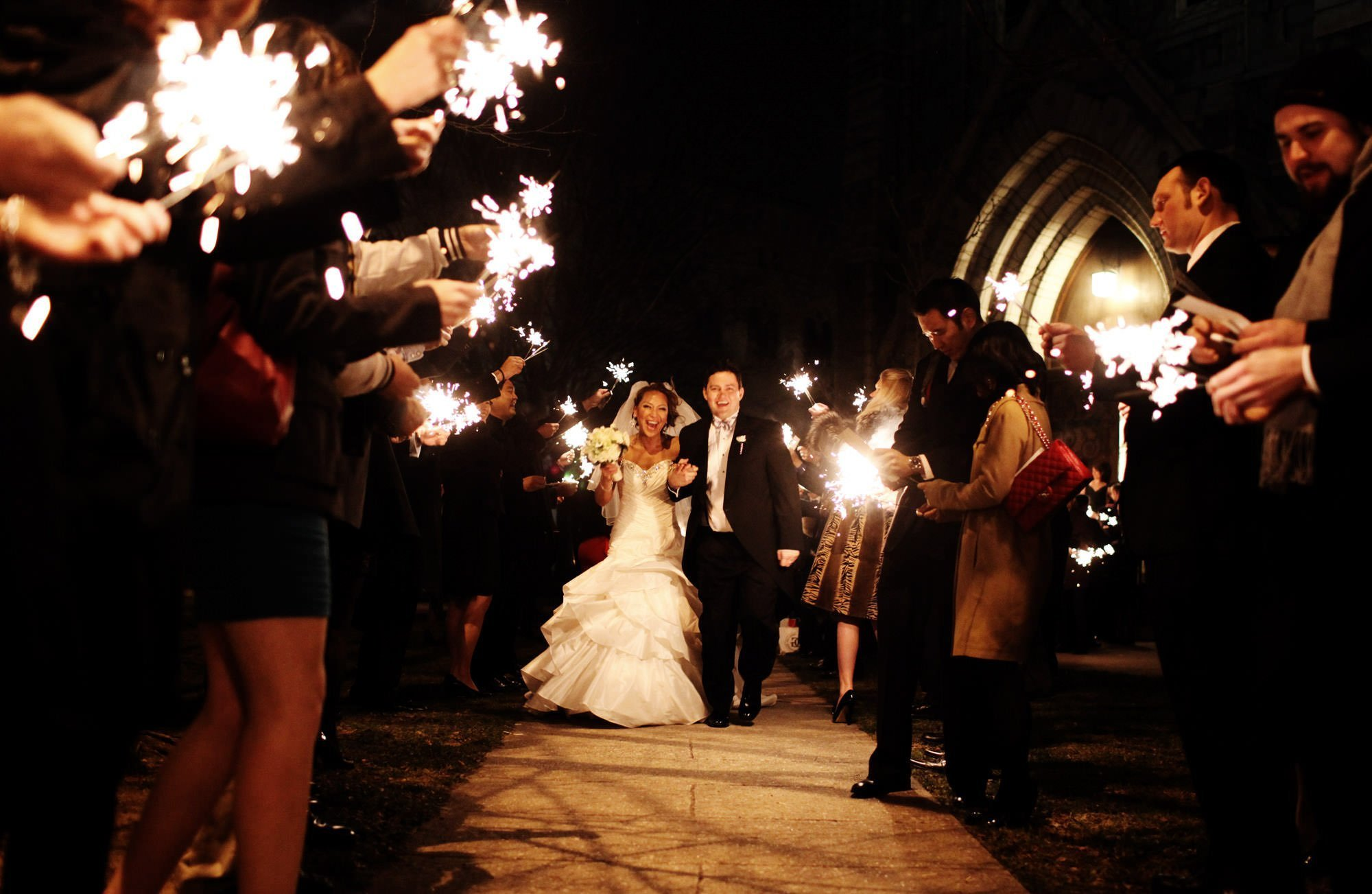 The bride and groom walk through sparklers after their wedding ceremony at Corpus Christi Church in Baltimore, MD.