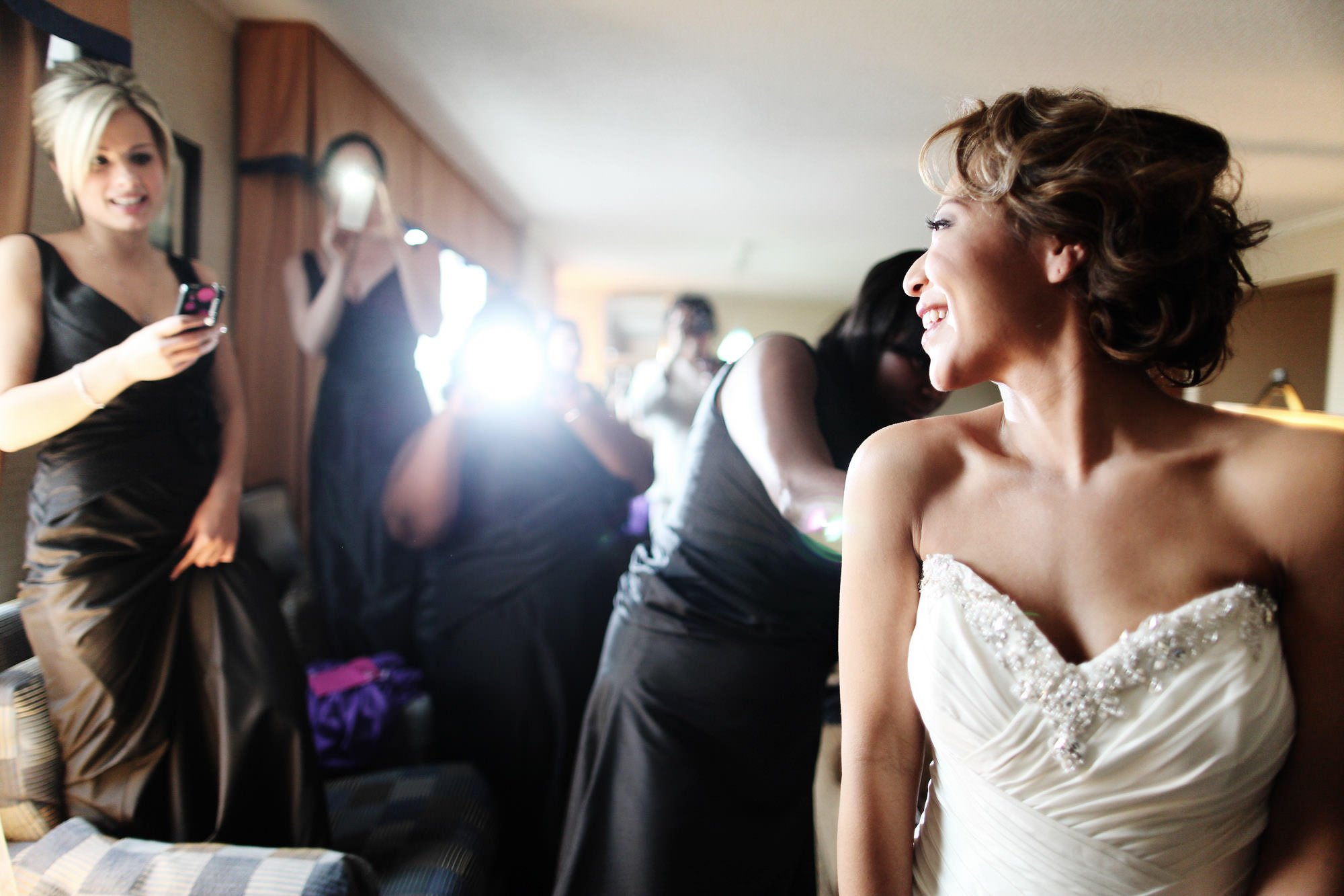 The bride looks at her bridesmaids while putting on her dress before her George Peabody Library wedding reception.