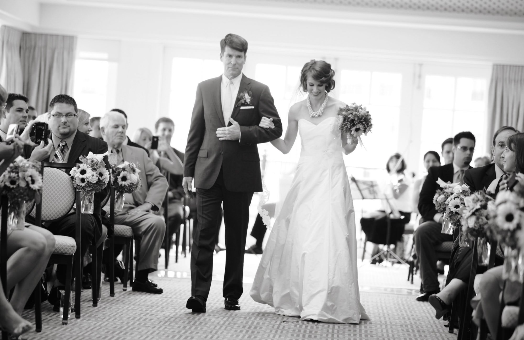 The bride is escorted down the aisle by her father during the ceremony at the Hay Adams hotel.