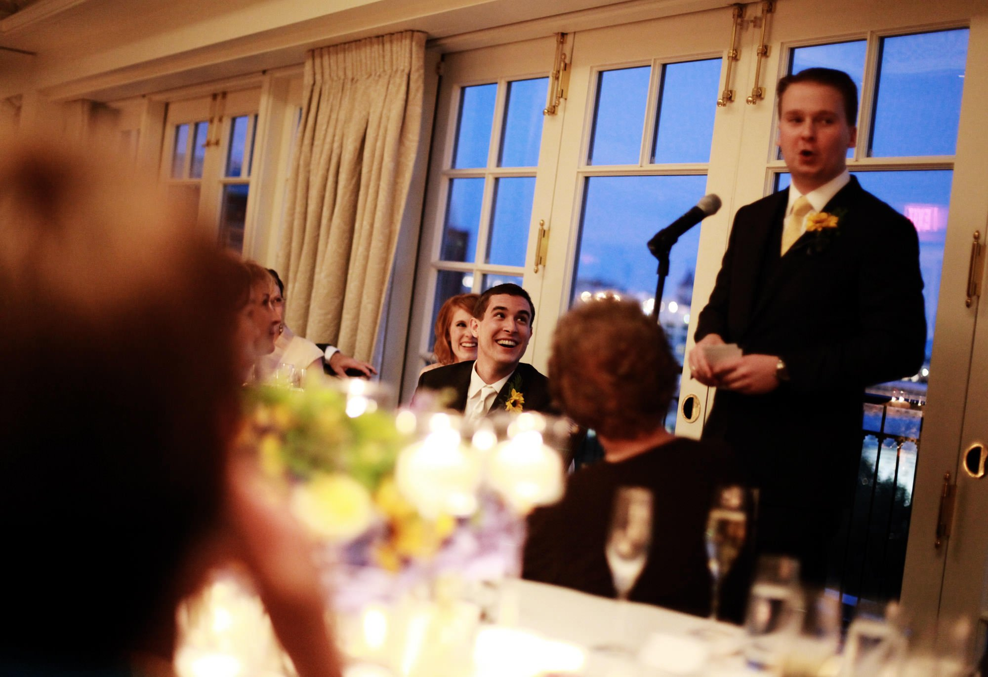 The groom listens to toasts during the wedding reception.