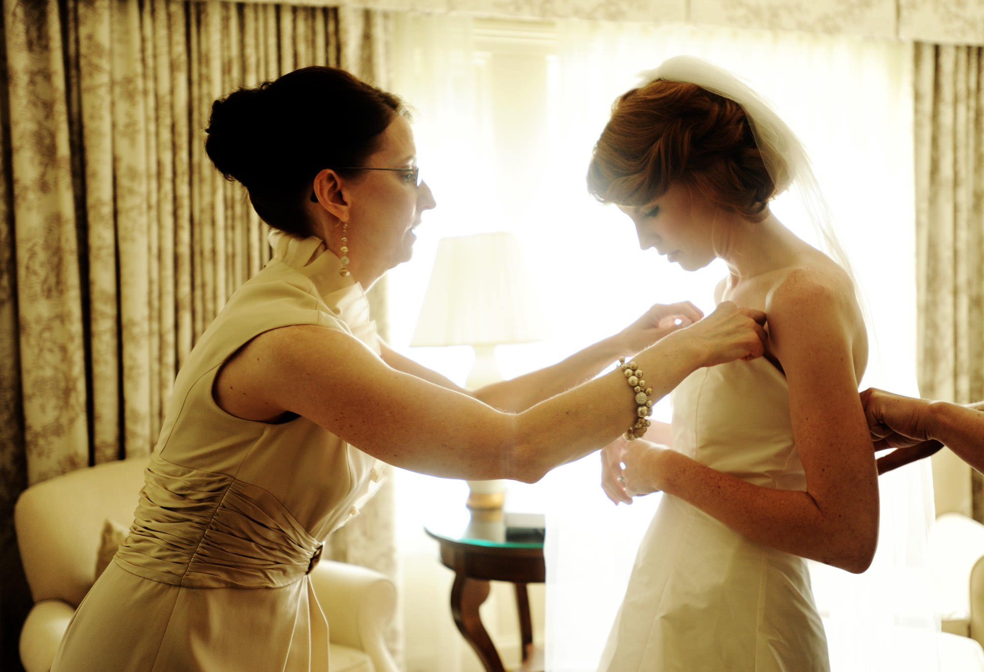 The bride puts on her dress before her Hay Adams wedding ceremony.
