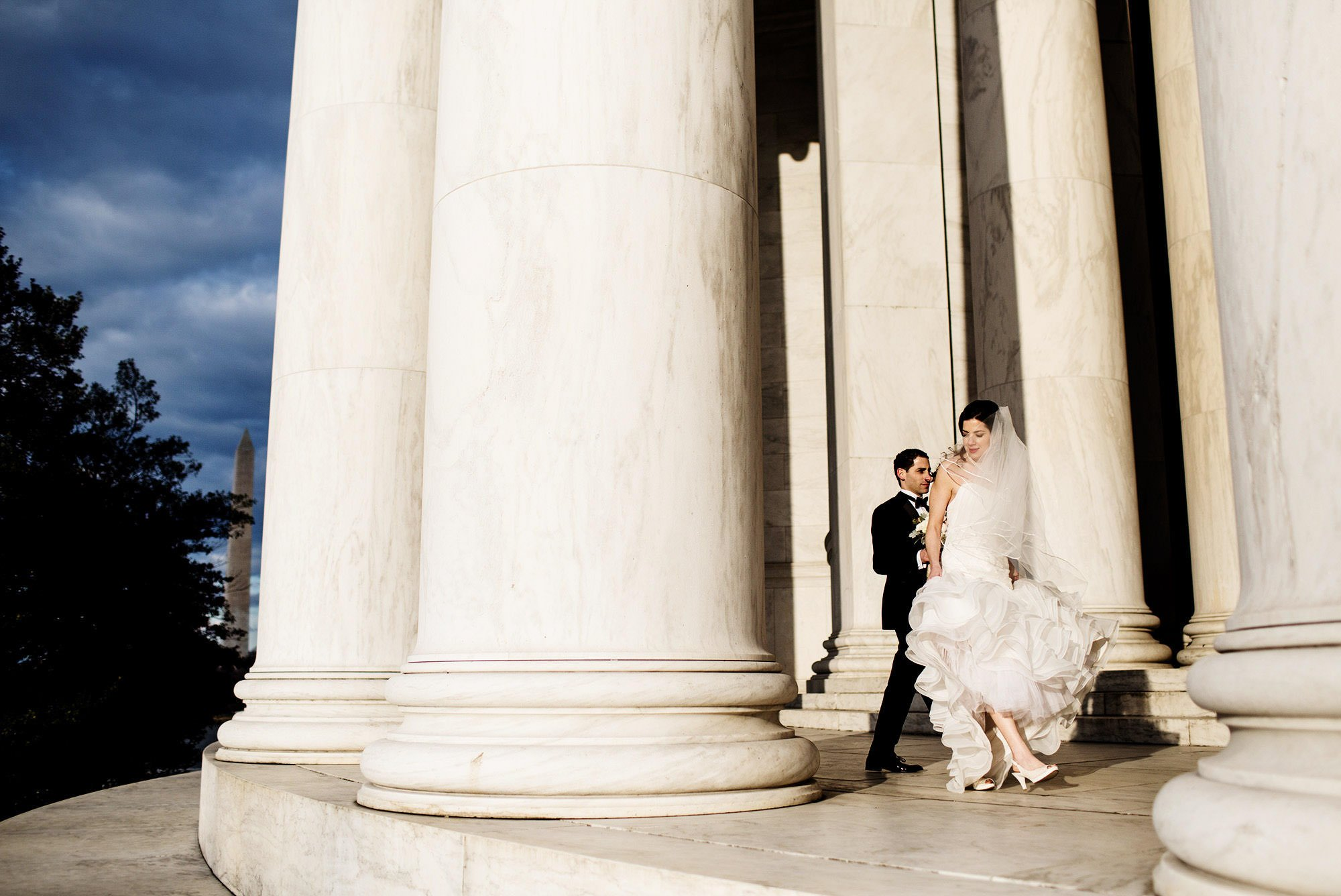 The bride and groom walk along the Jefferson Memorial in Washington, DC before their NMWA wedding.