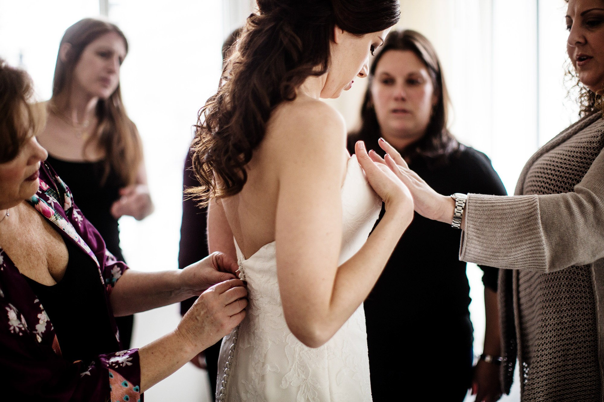 The bride puts on her wedding dress at the Sofitel in Washington, DC prior to the NMWA wedding.