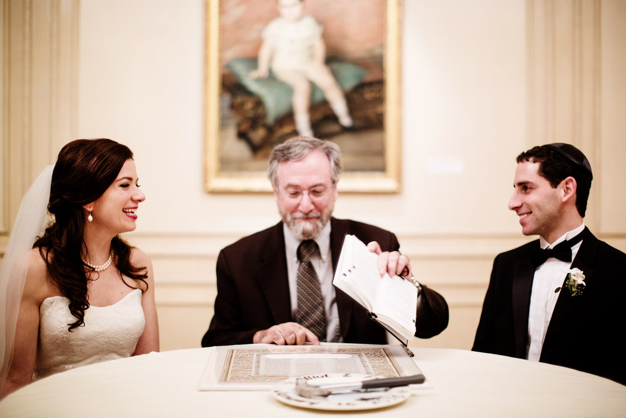 The bride and groom participate in a ketubah signing during their NMWA DC wedding.