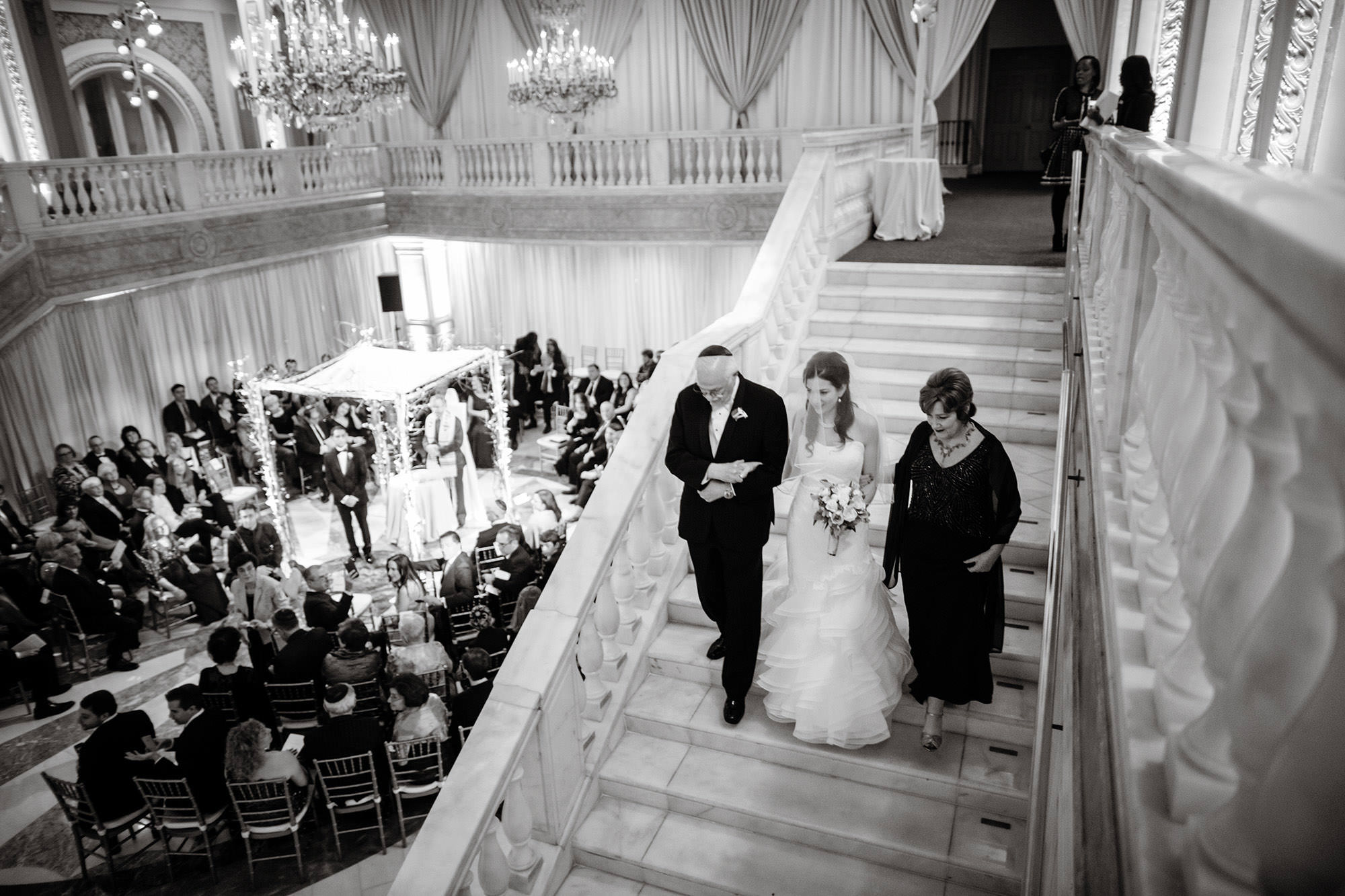 The bride is escorted down the steps of NMWA during her wedding ceremony.
