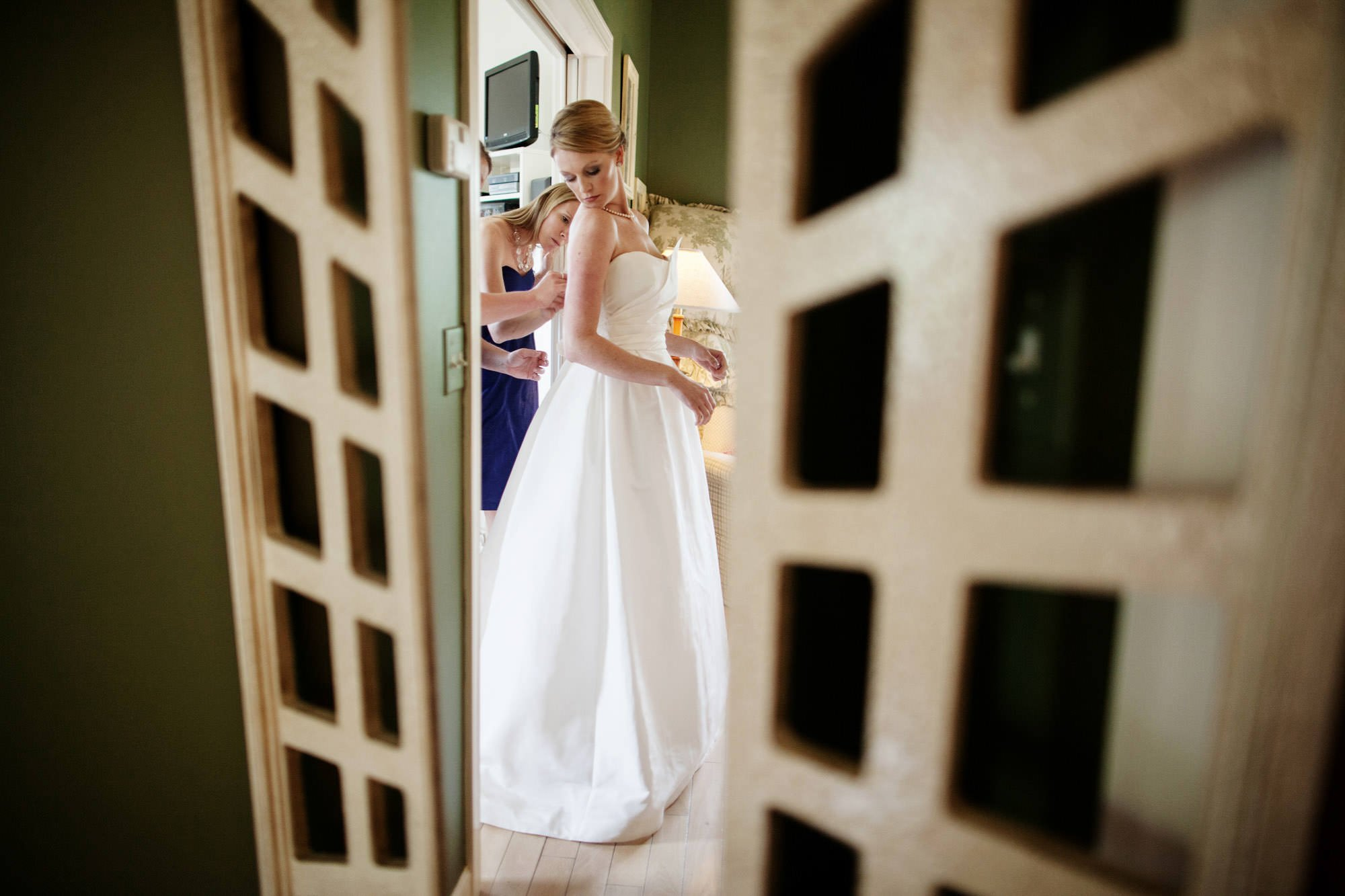 The bride puts on her wedding dress during her Oaks Waterfront Inn and Events Wedding.