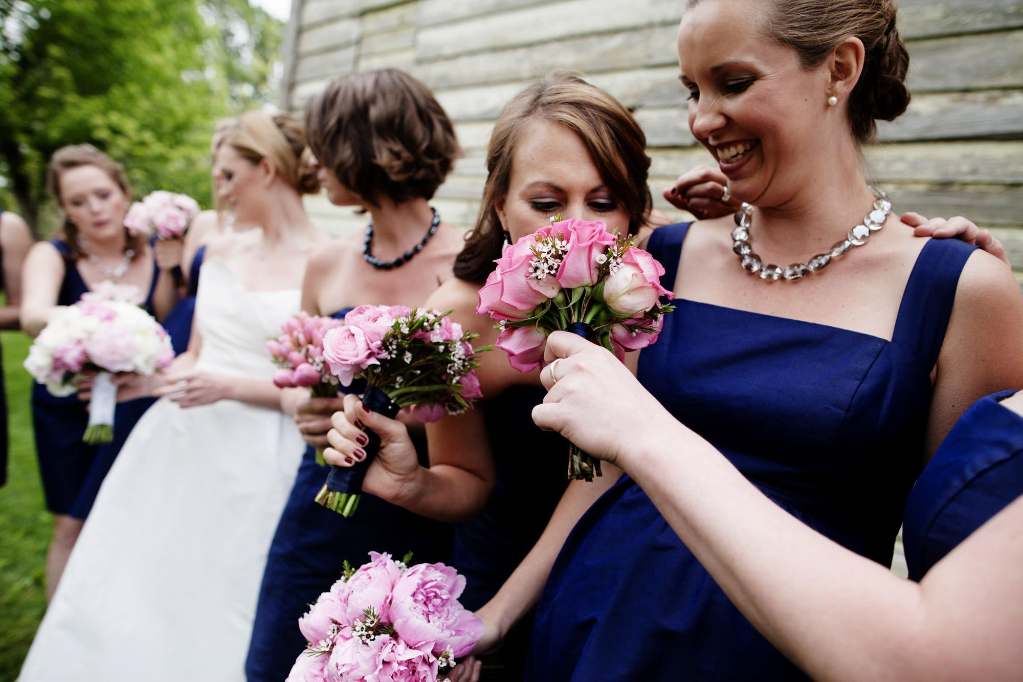 The bridesmaids smell each other's flowers on the Oaks Waterfront Inn and Events Wedding day.