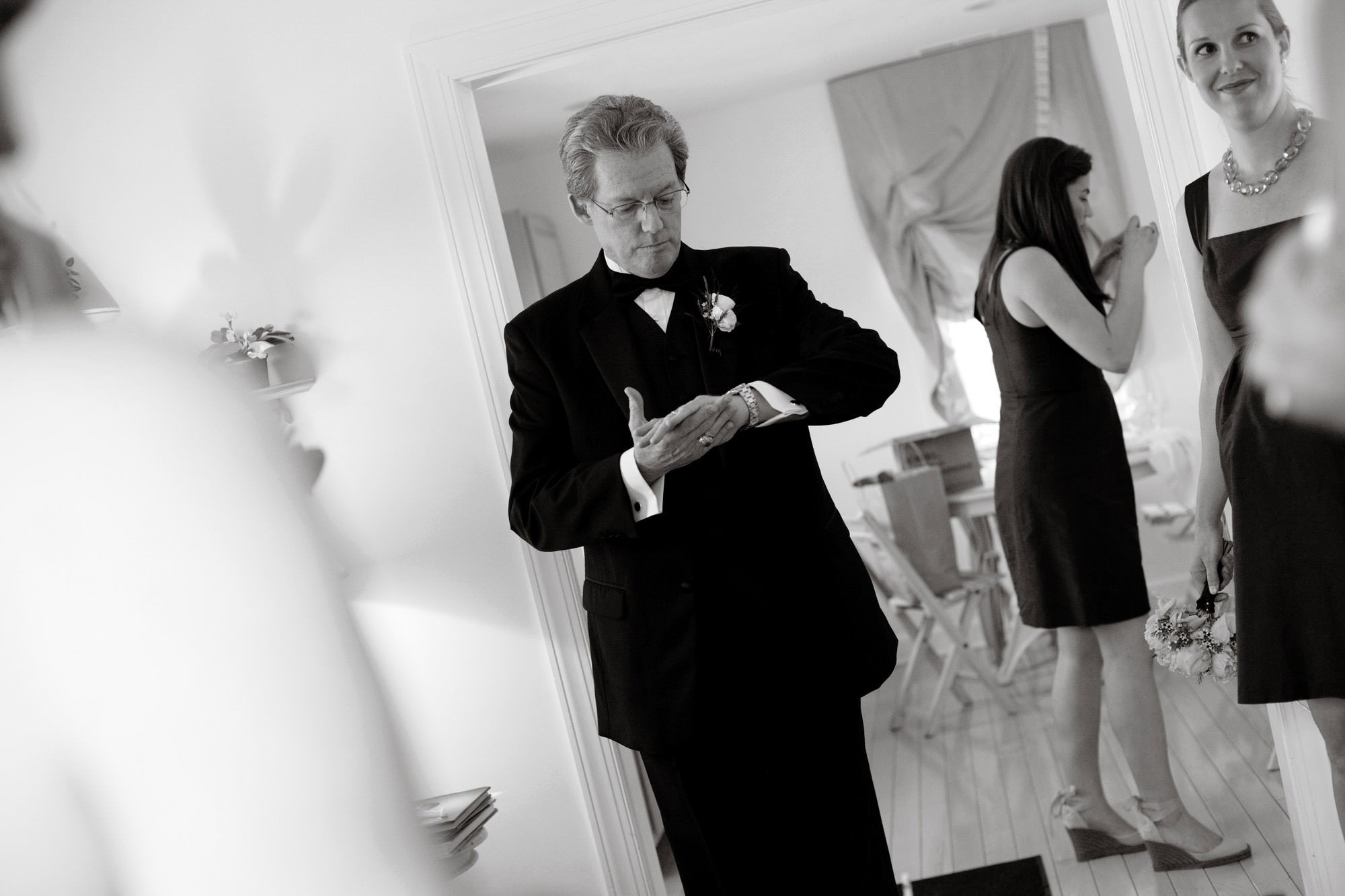 The father of the bride checks his watch before the Oaks Waterfront Inn and Events Wedding ceremony.