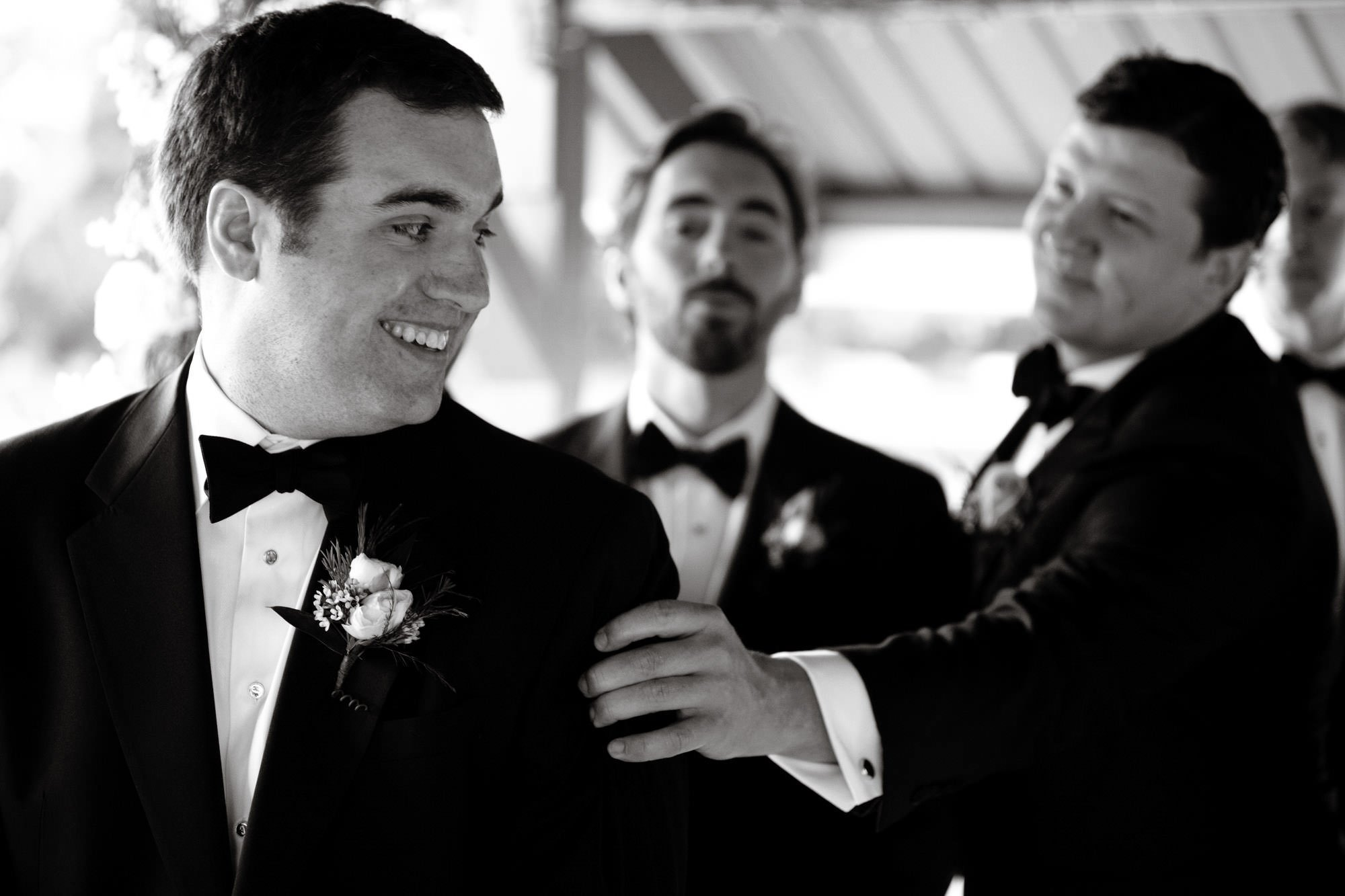 The groom is consoled by one of his groomsmen during the Oaks Waterfront Inn and Events Wedding ceremony.