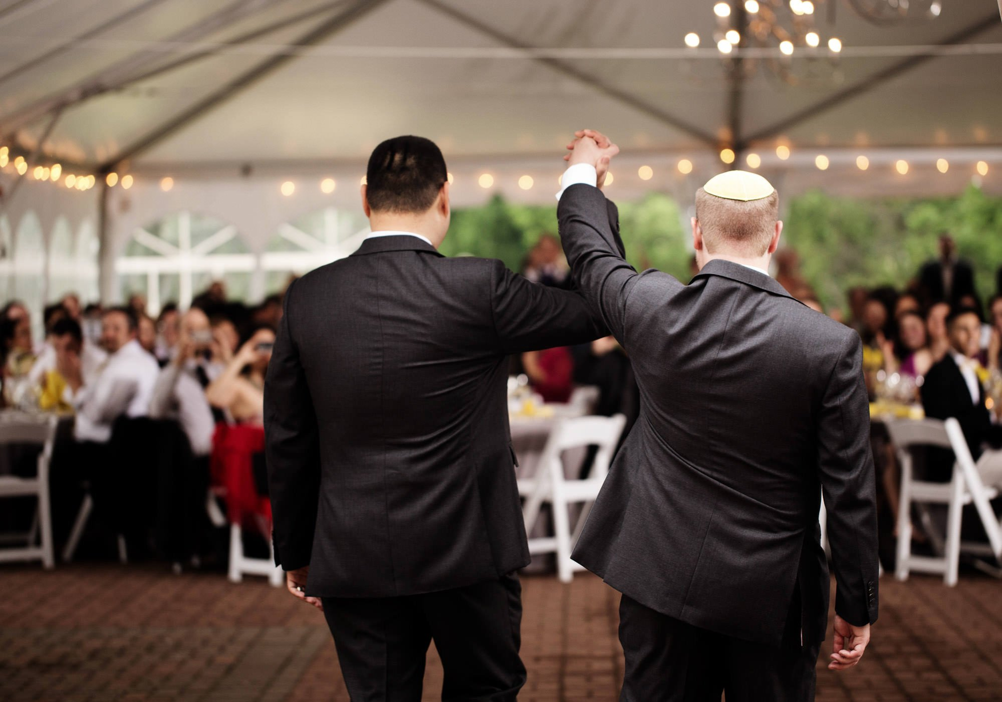The grooms are introduced to the tented reception at Oxon Hill Manor.
