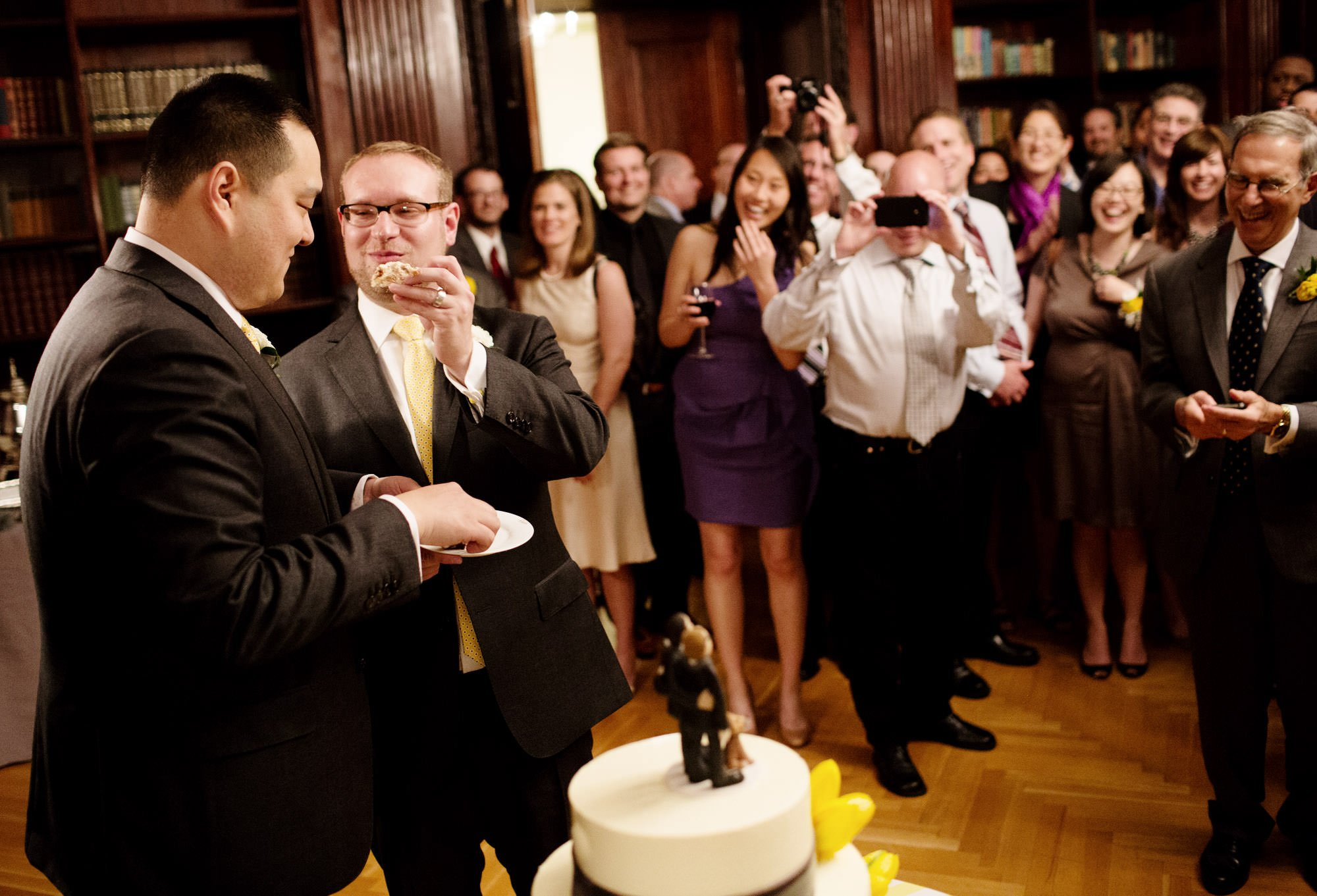 The grooms cut their wedding cake as guests look on during their reception at Oxon Hill Manor.