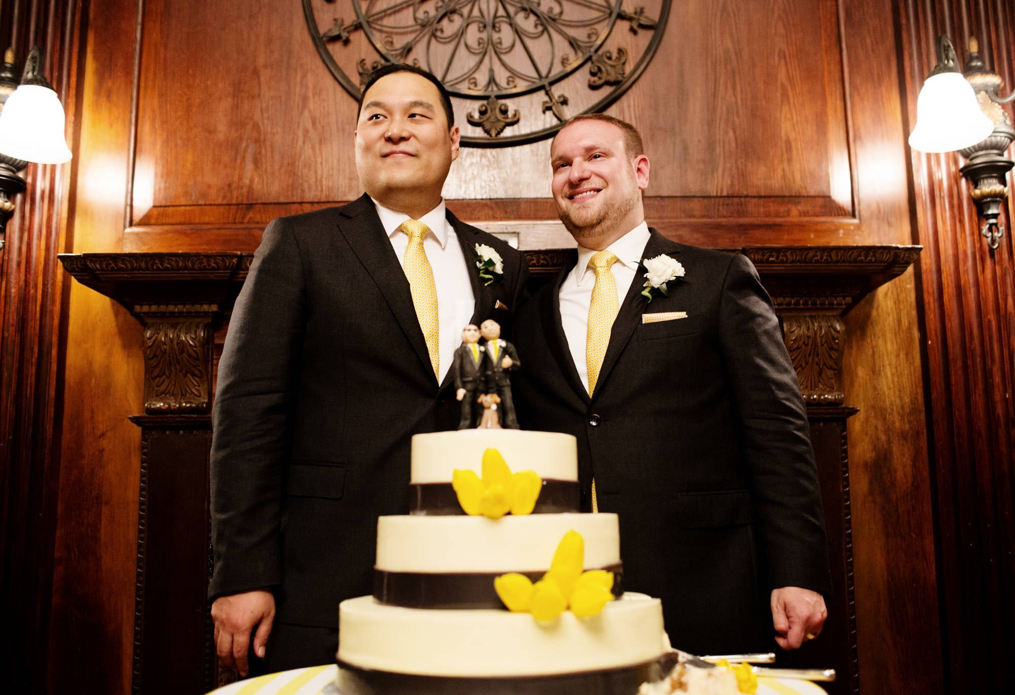 The two grooms prepare to cut the cake during their Oxon Hill Manor wedding.