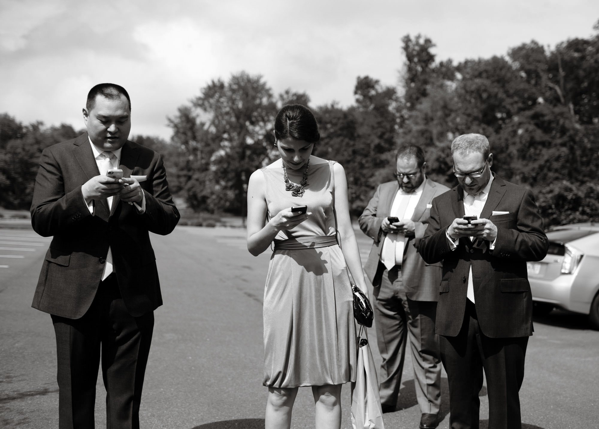 The wedding party looks at their phones in the parking lot of Oxon Hill Manor.