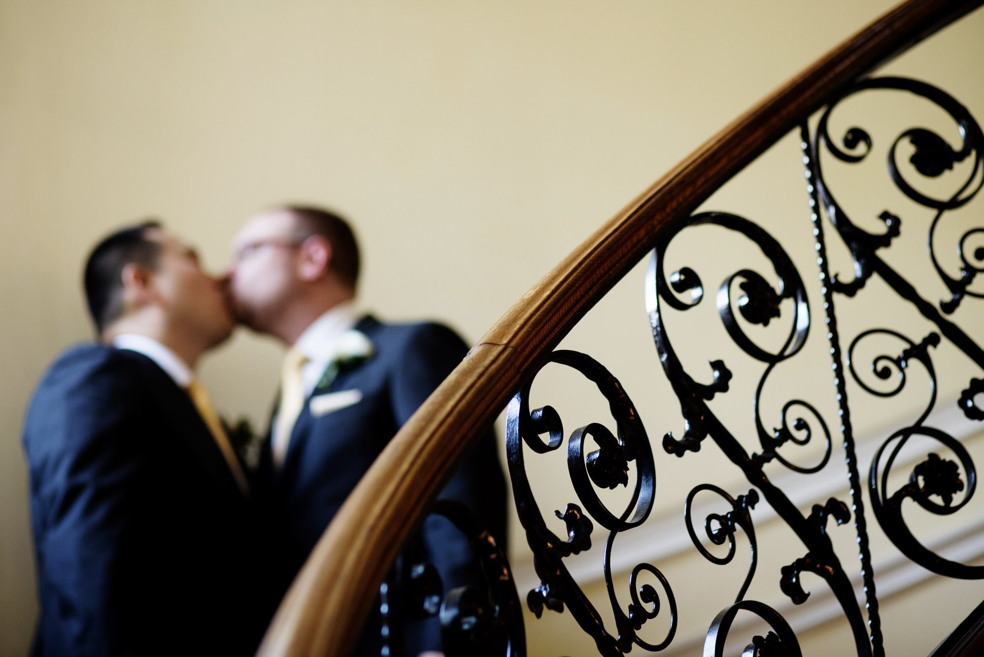 The grooms kiss during a portrait at Oxon Hill Manor.