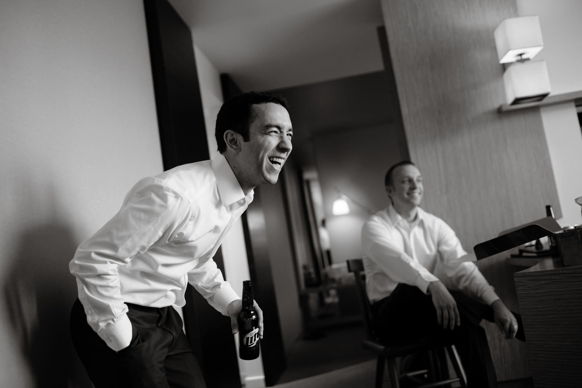 The groom laughs with his groomsmen while getting ready on his Park Hyatt Washington DC Wedding day.