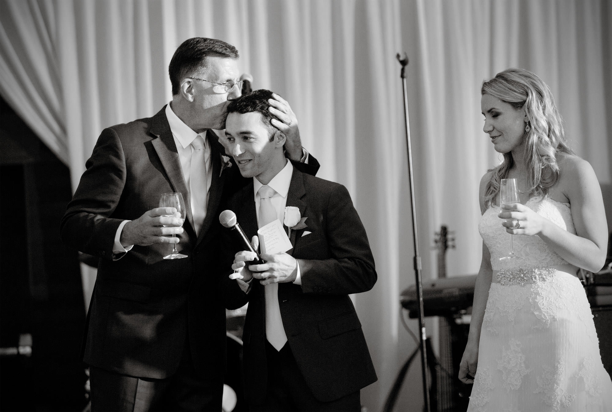 The groom is hugged by the father of the bride during the Park Hyatt DC wedding reception.