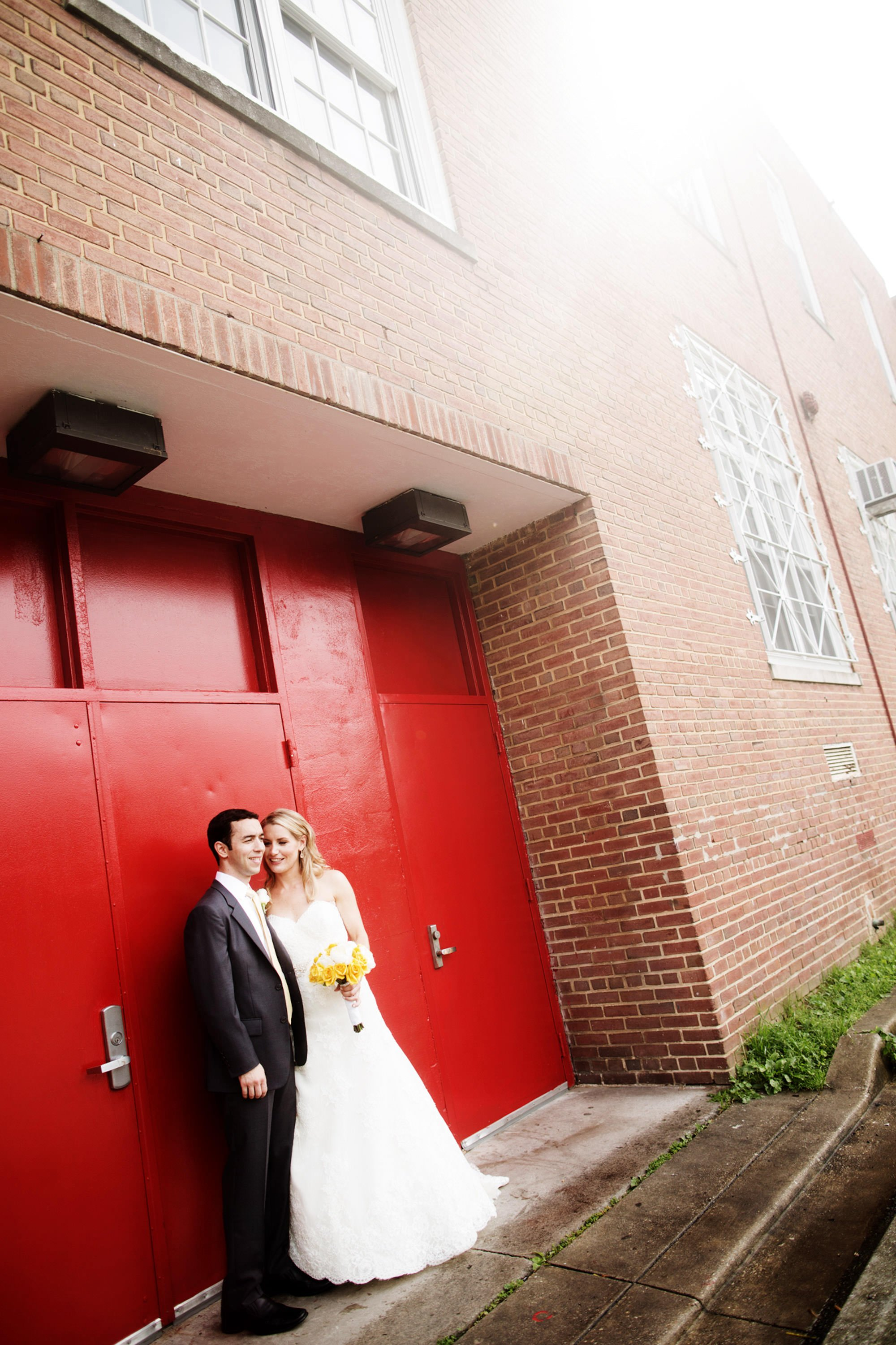 The couple poses for a portrait in front of red doors before their Park Hyatt Washington DC Wedding.