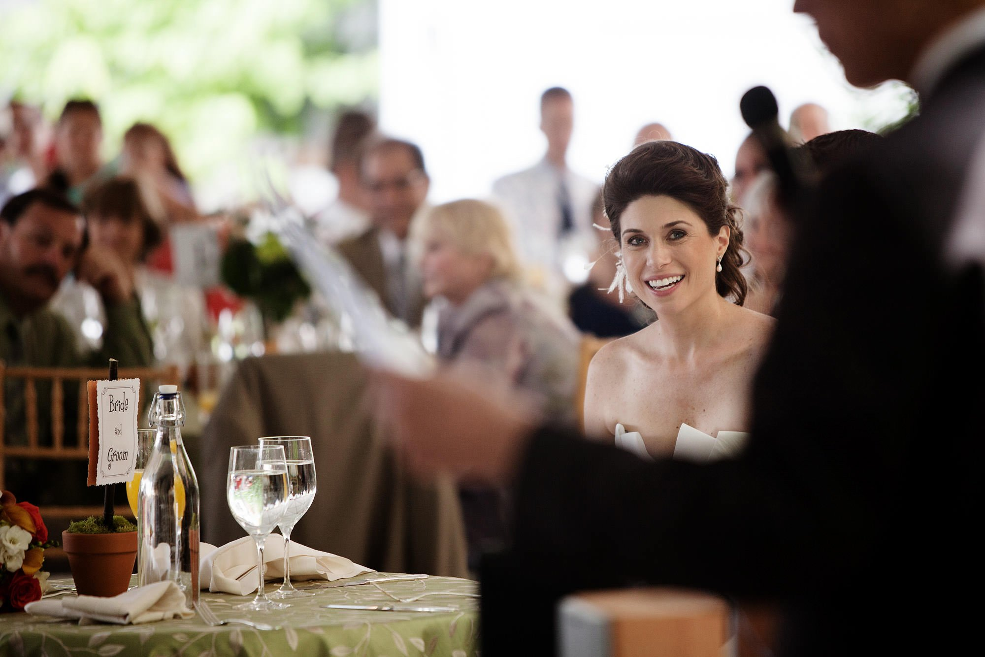 The bride listens to toasts during the River Farm Alexandria Wedding reception.
