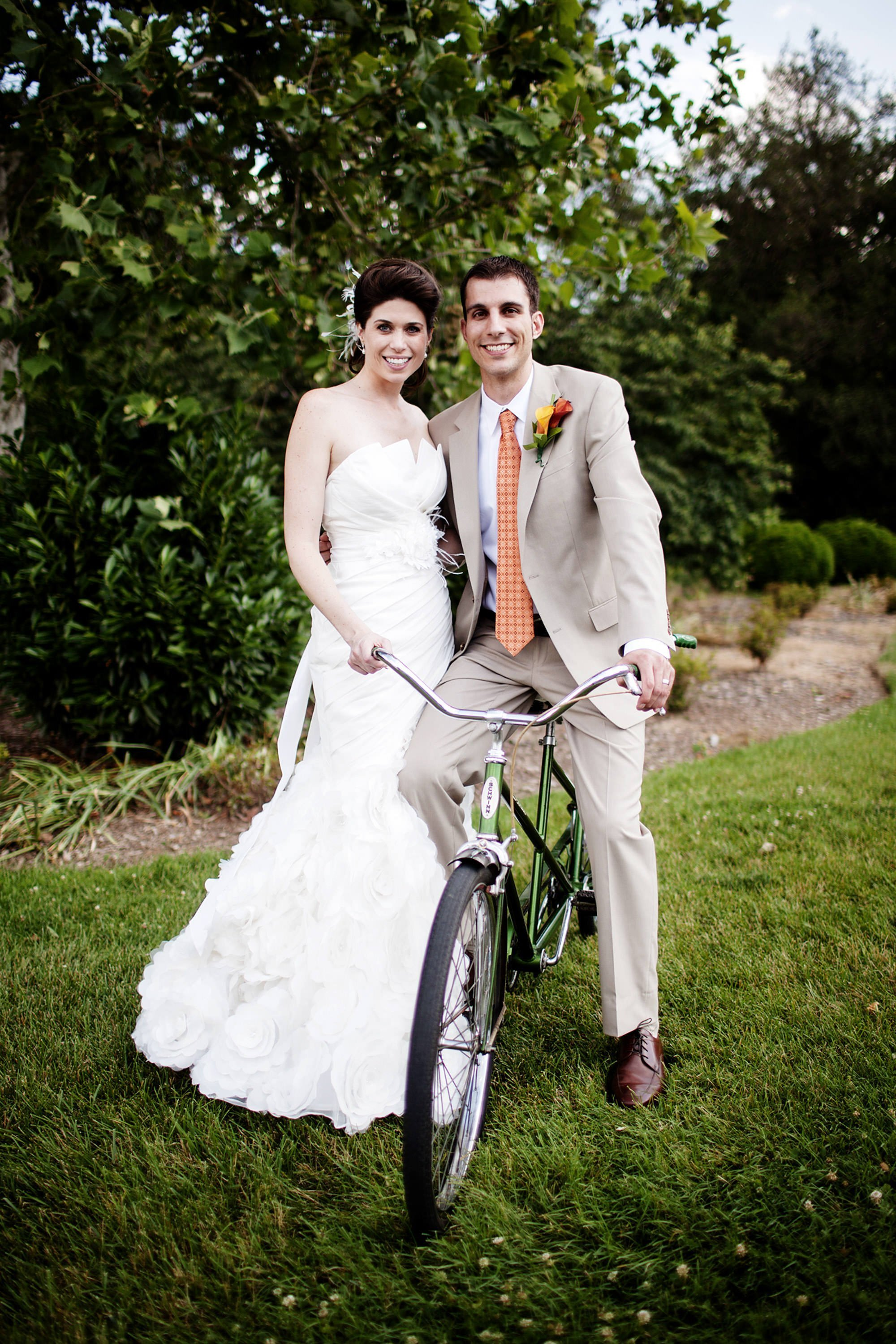 The groom sits on an old Schwinn bicycle after the reception at their River Farm Alexandria Wedding.