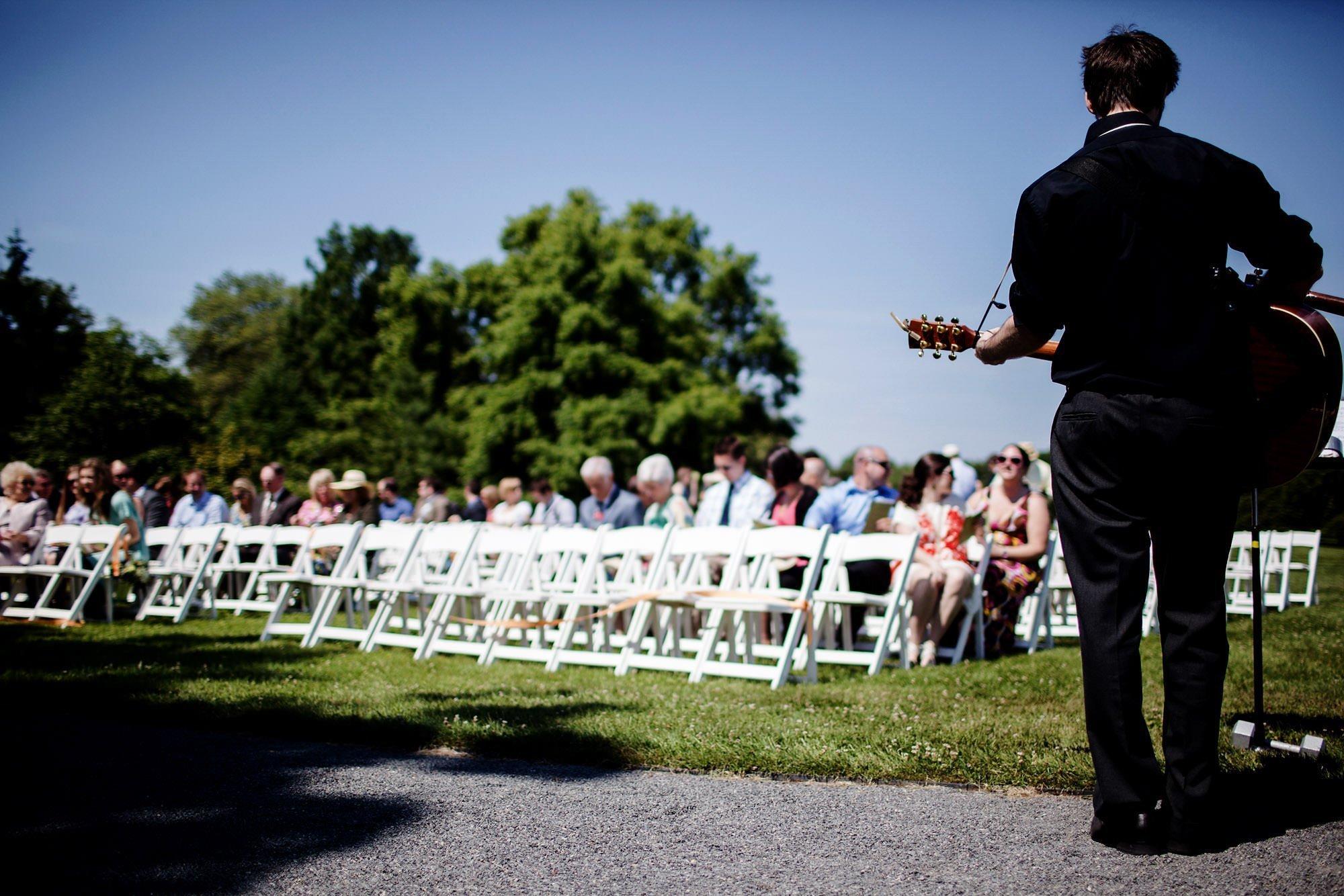 A musician plays the guitar during the River Farm Alexandria Wedding ceremony.