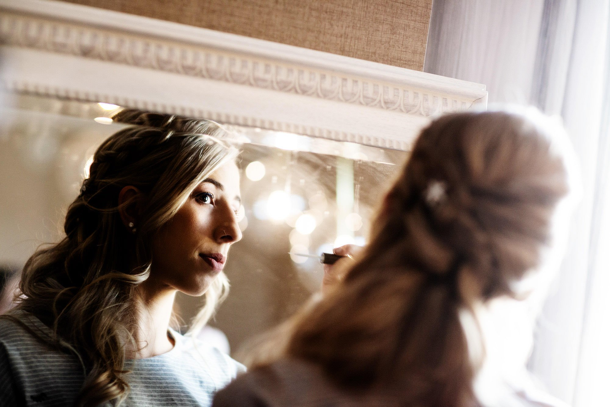 A bridesmaid puts on her makeup.