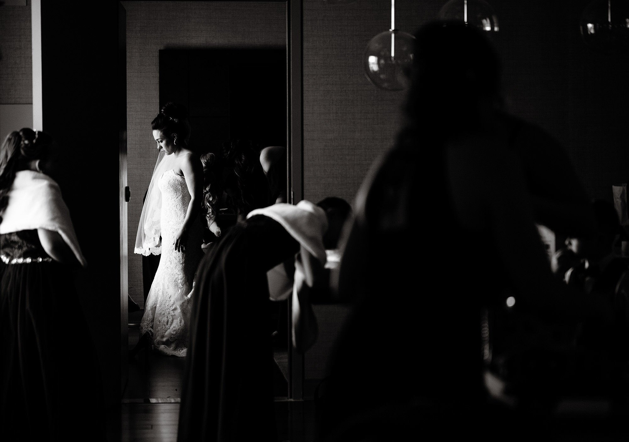 The bride puts on her dress before the wedding ceremony at the Meeting House at Olde Mistick Village.