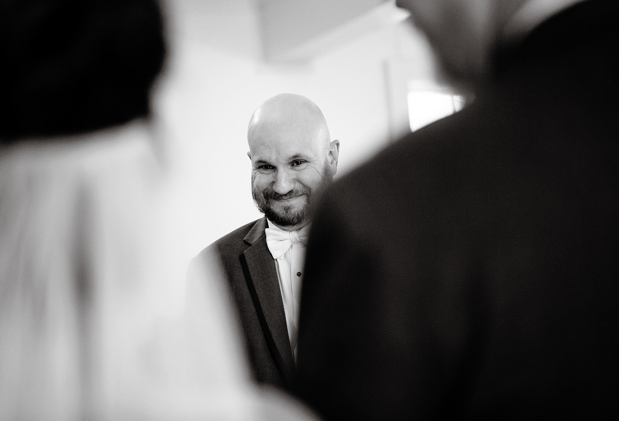 The groom smiles at his bride during the wedding ceremony at the Meeting House at Olde Mistick Village.