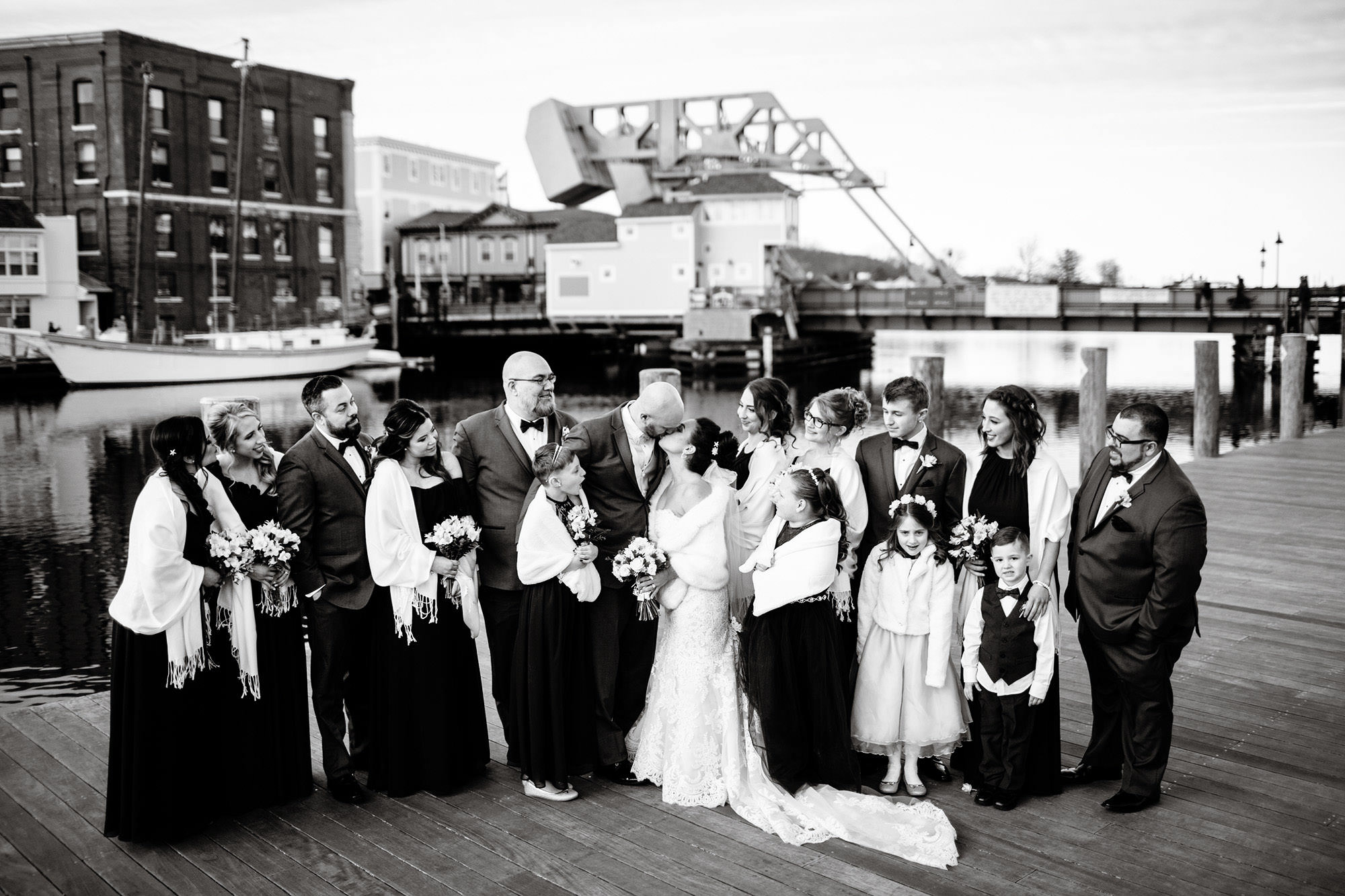 The wedding party stands on the dock as the couple kisses in Downtown Mystic, CT.