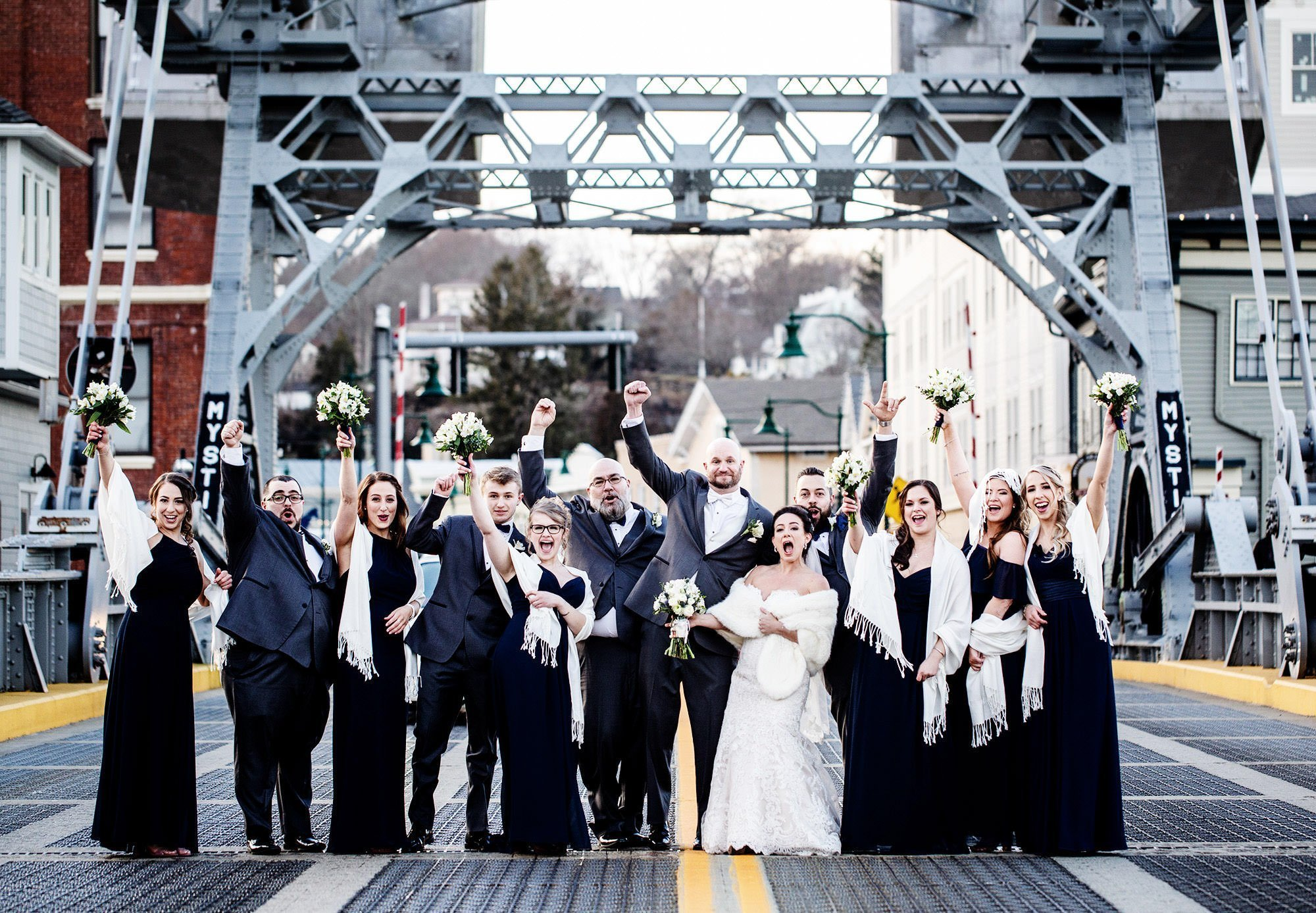 The wedding party cheers on the bridge in Downtown Mystic by the drawbridge.