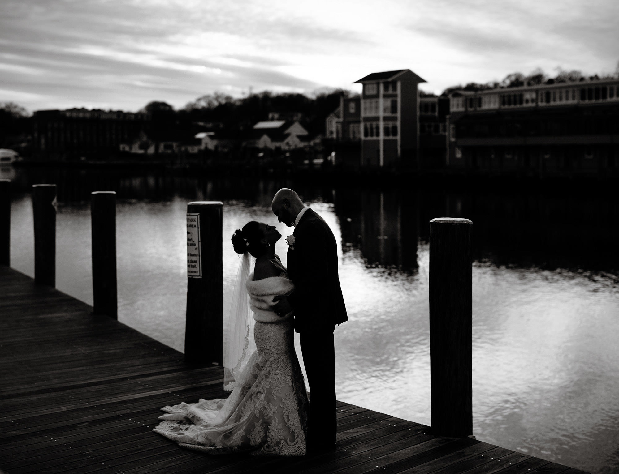 The couple stands on the dock in Mystic, CT before the wedding reception at Silver Oak Mystic.