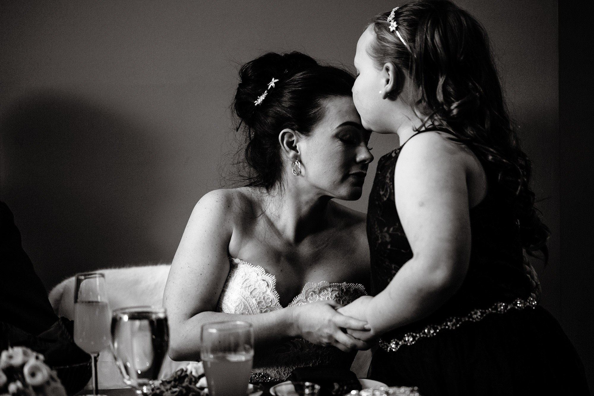 The bride is kissed by her daughter during the Silver Oak Mystic wedding reception.