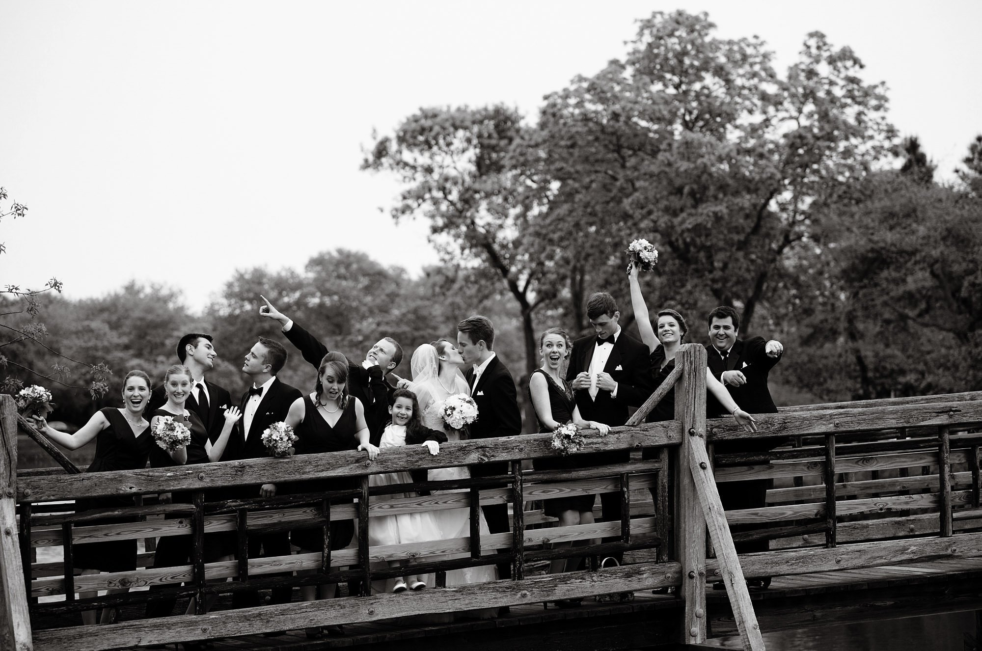The wedding party poses for portraits on the walking bridge in Divine Park before their Spring Lake Bath and Tennis Club wedding reception.