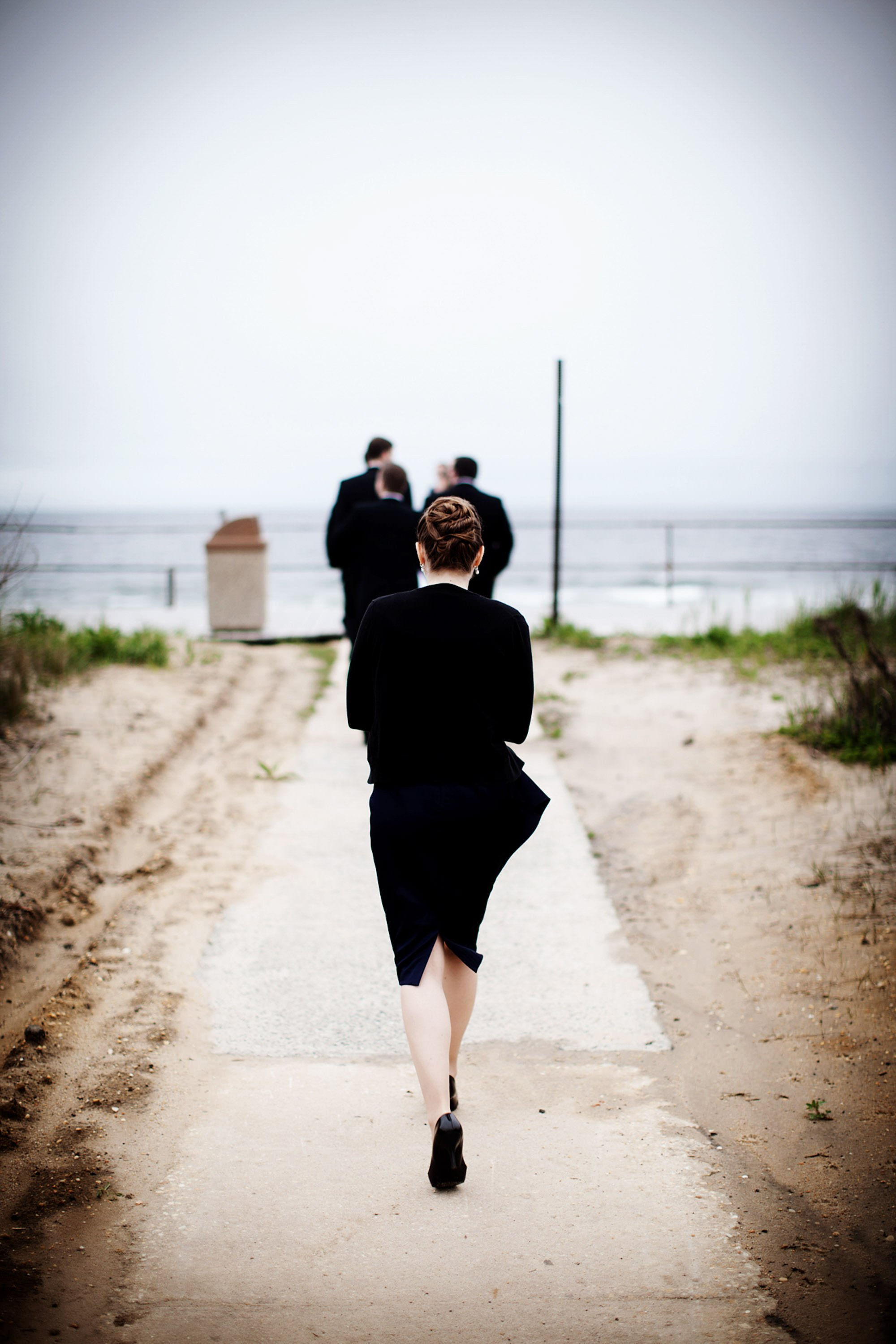 A bridesmaid makes her way to the beach before the Spring Lake Bath and Tennis Club wedding reception.