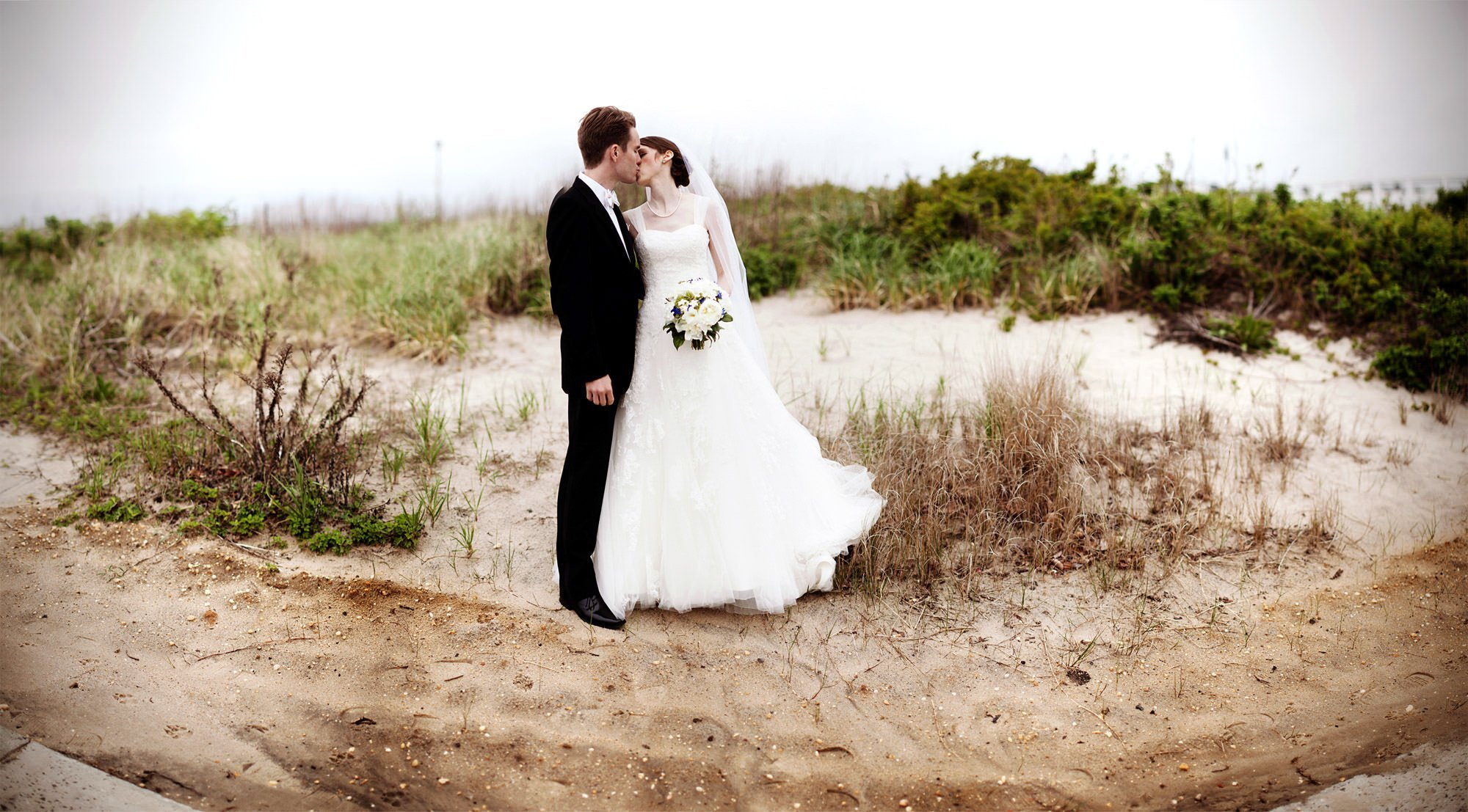 The bride and groom kiss on the beach before their Spring Lake Bath and Tennis Club wedding reception.