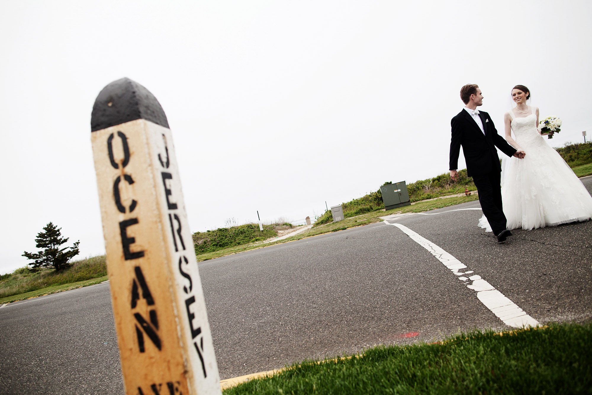 The bride and groom cross a street in Spring Lake before their Spring Lake Bath and Tennis Club wedding reception.