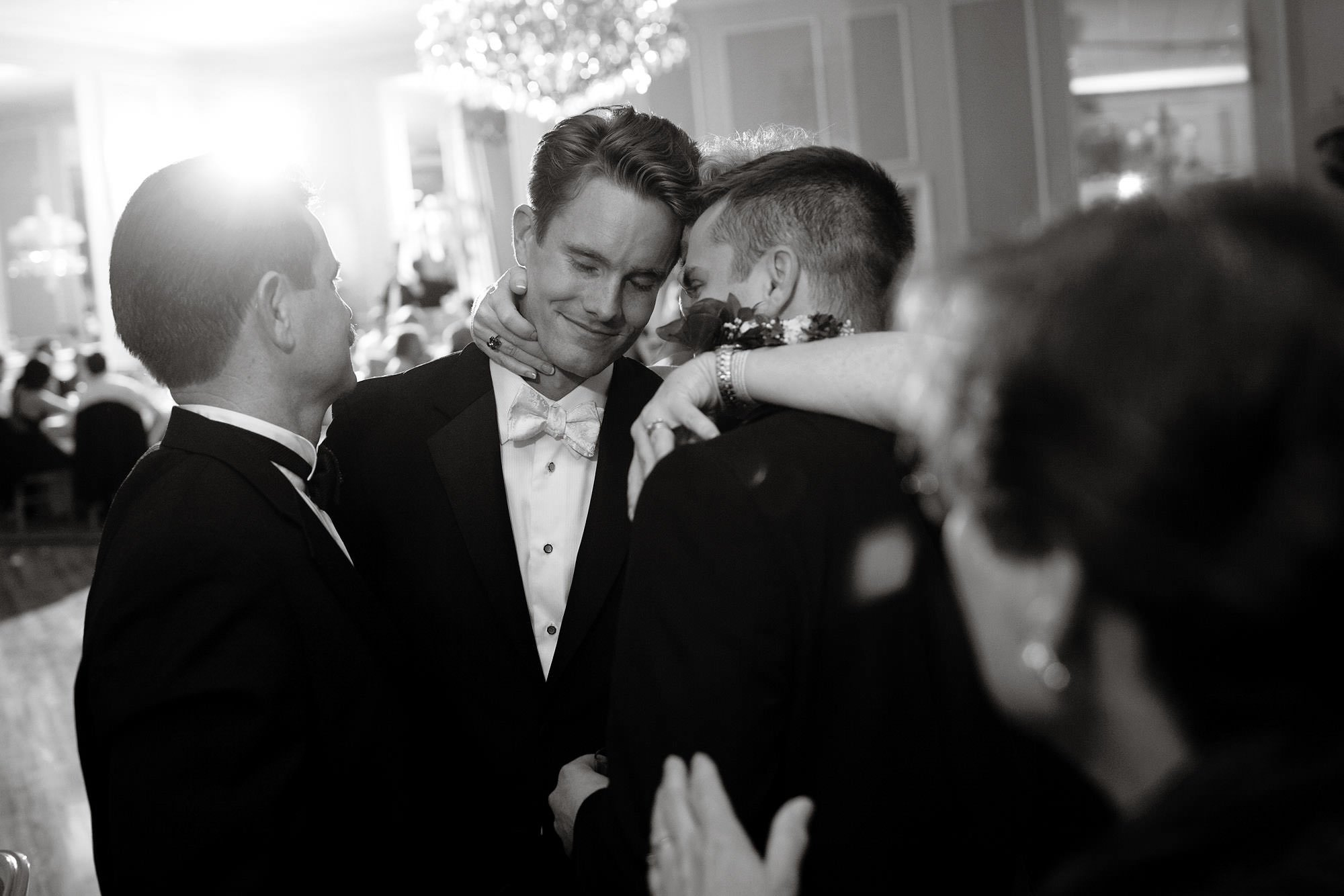 The groom receives a hug from his family during his Spring Lake Bath and Tennis Club wedding reception.