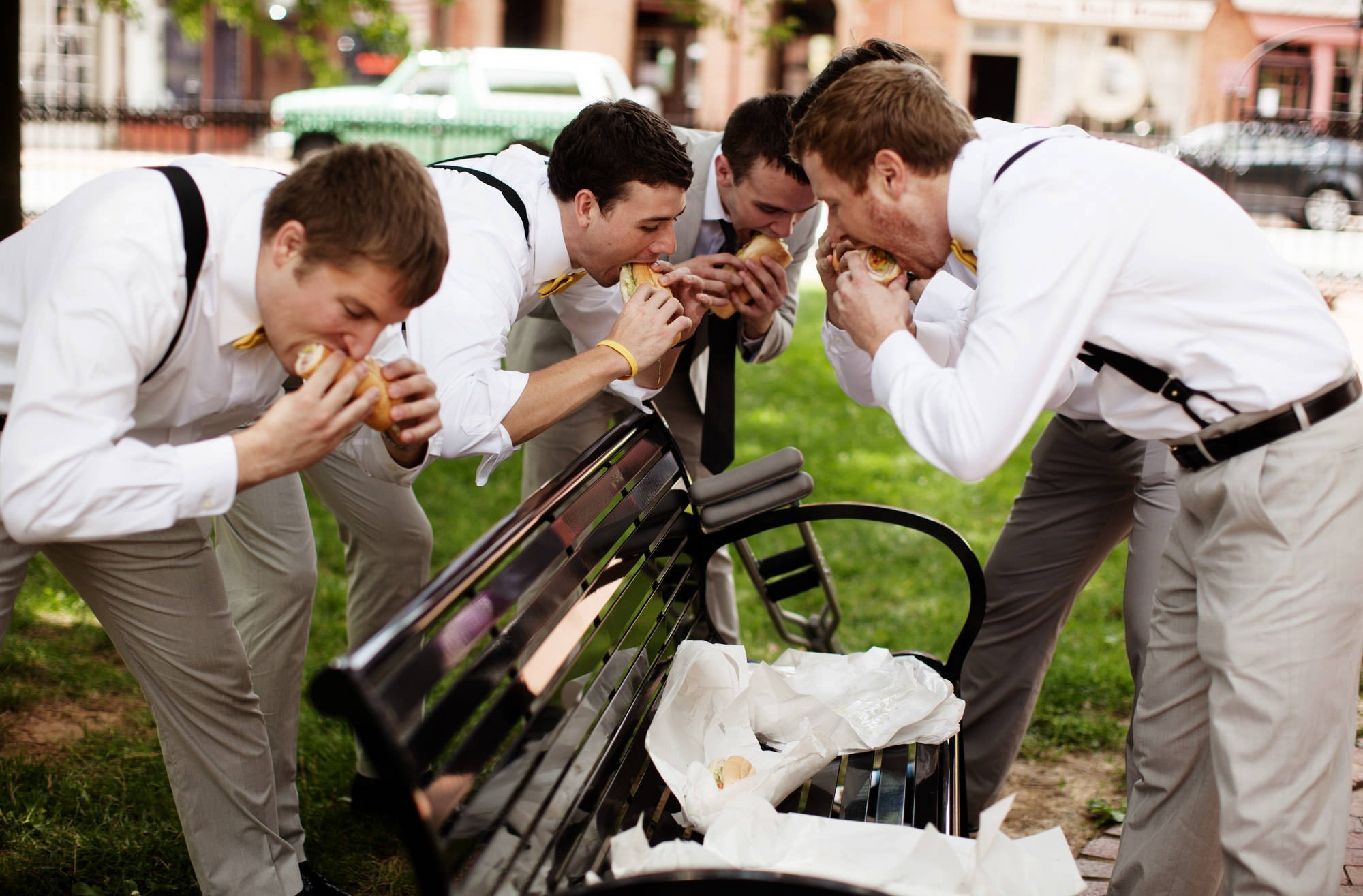 Groomsmen eat sandwiches in a park in Downtown Leesburg before the wedding at Sunset Hills Vineyard.