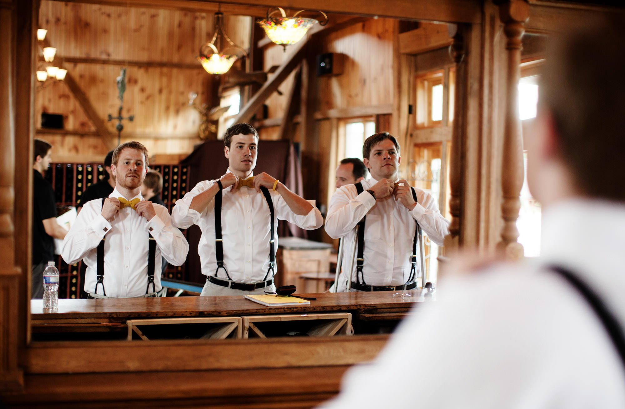 Groomsmen adjust their bowties before the ceremony of this Sunset Hills Vineyard.