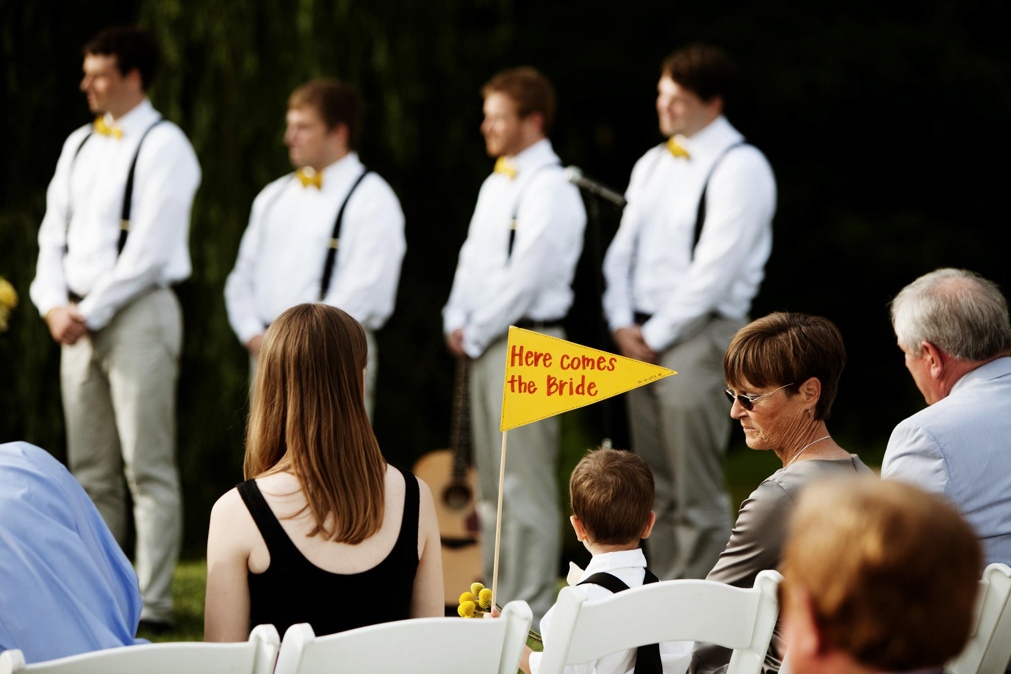 The ring bearer holds up a sign during the wedding reception at Sunset Hills Vineyard.