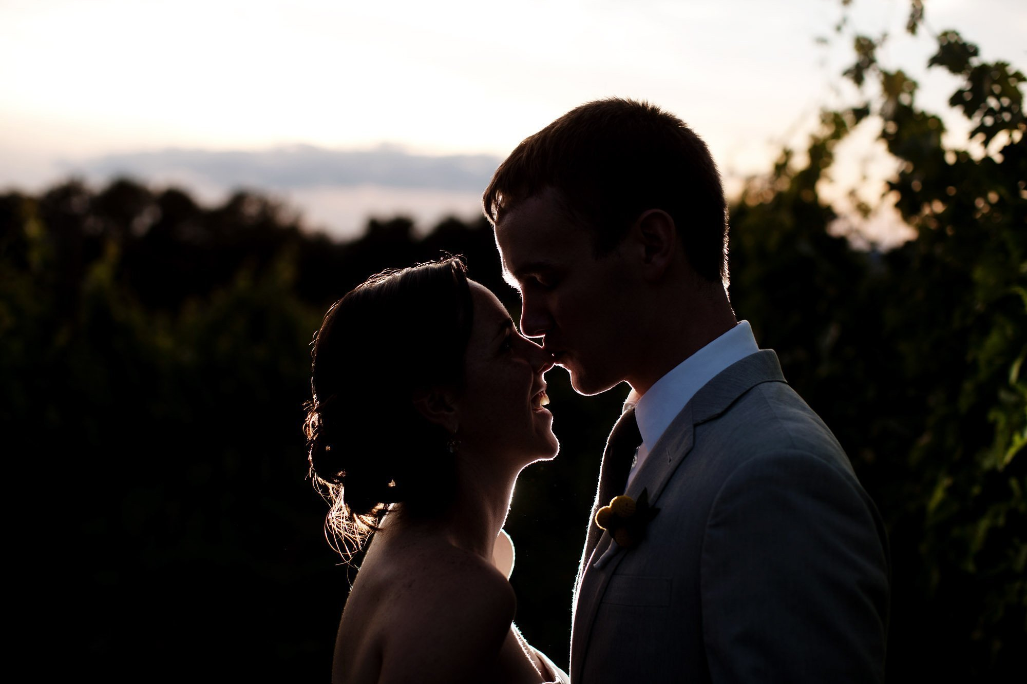 The bride and groom kiss during sunset in the field during their Sunset Hills Vineyard wedding.