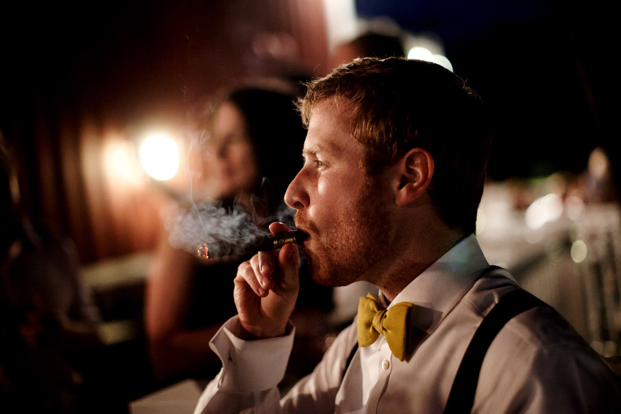 A groomsman smokes a cigar during the wedding reception at Sunset Hills Vineyard.