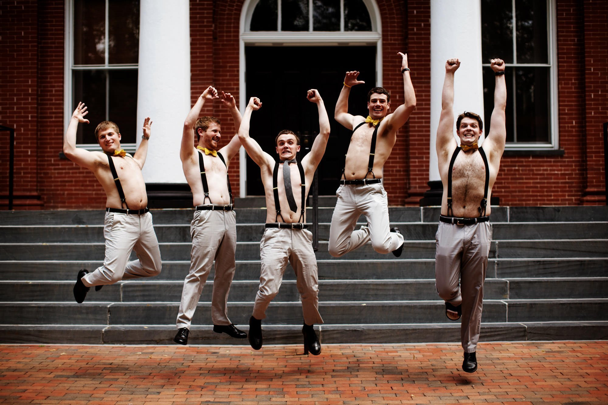 The groom jumps with his groomsmen in downtown Leesburg prior to his Sunset Hills Vineyard wedding.