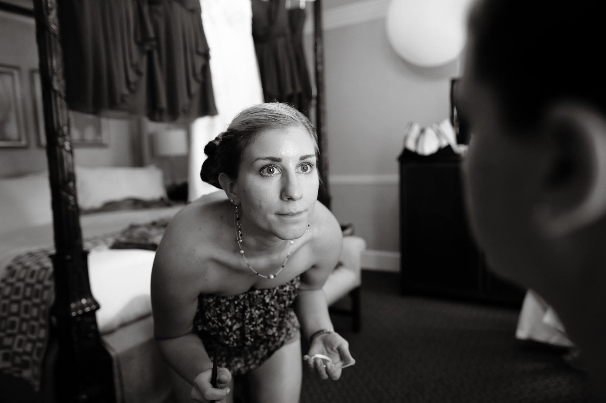 A bridesmaid puts on the bride's makeup prior to the wedding ceremony.