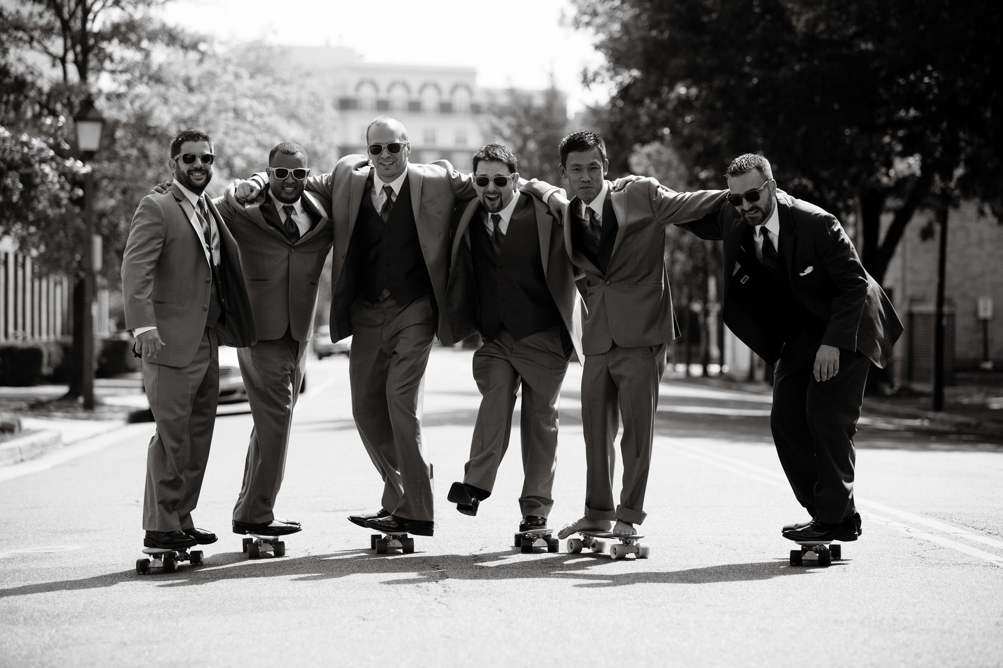The groom and his groomsmen pose on their skateboards before this Topedo Factory wedding.