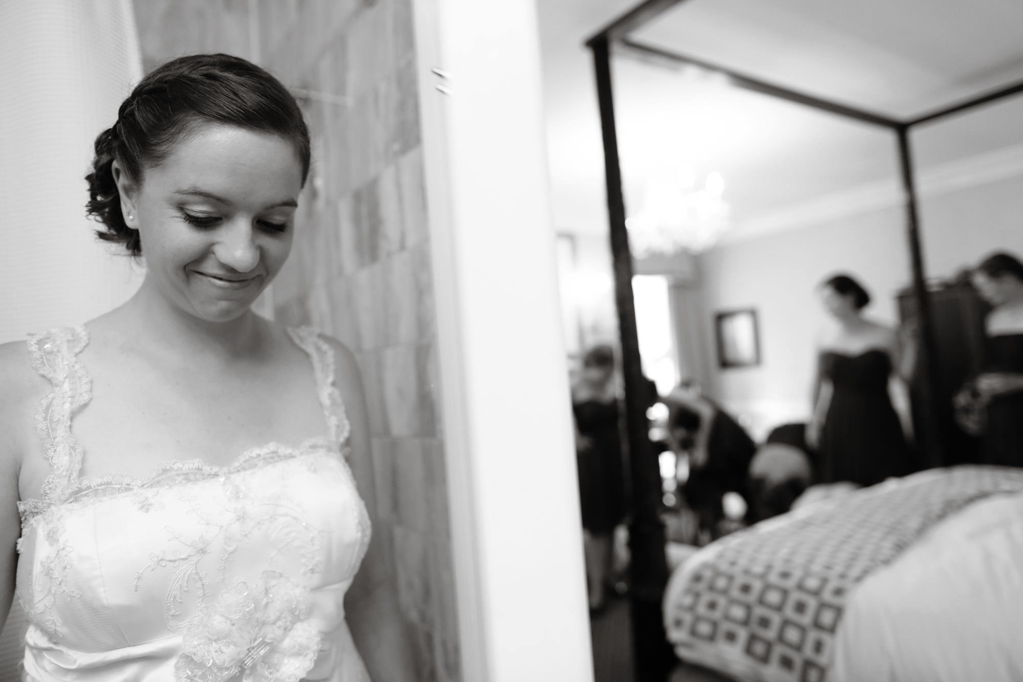 The bride smiles while putting on her wedding dress before the ceremony at Topedo Factory.