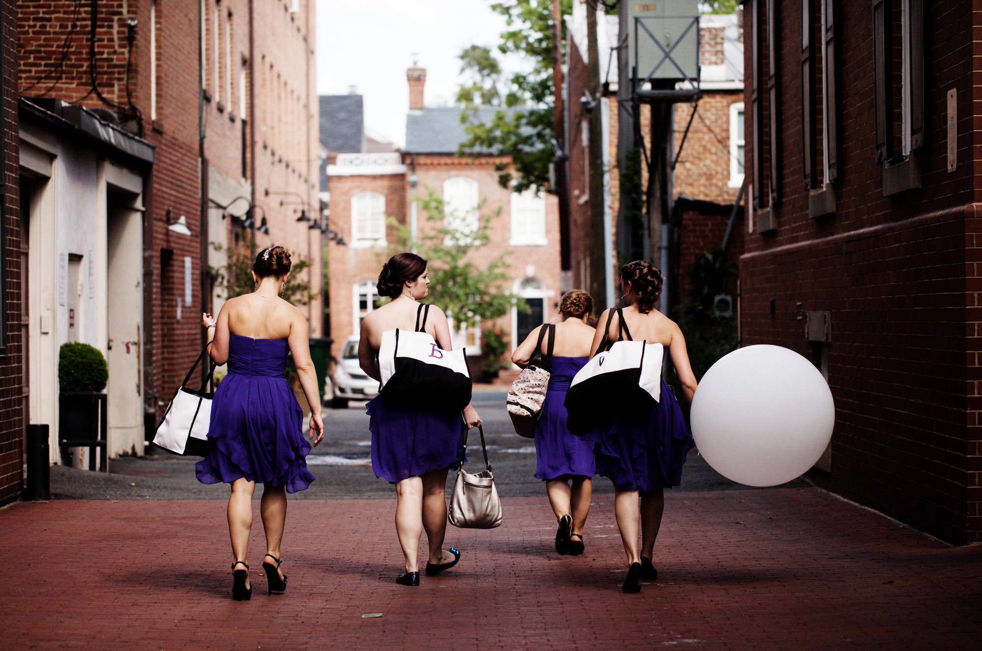 Bridesmaids walk through an alley carrying balloons before the wedding ceremony at Topedo Factory.