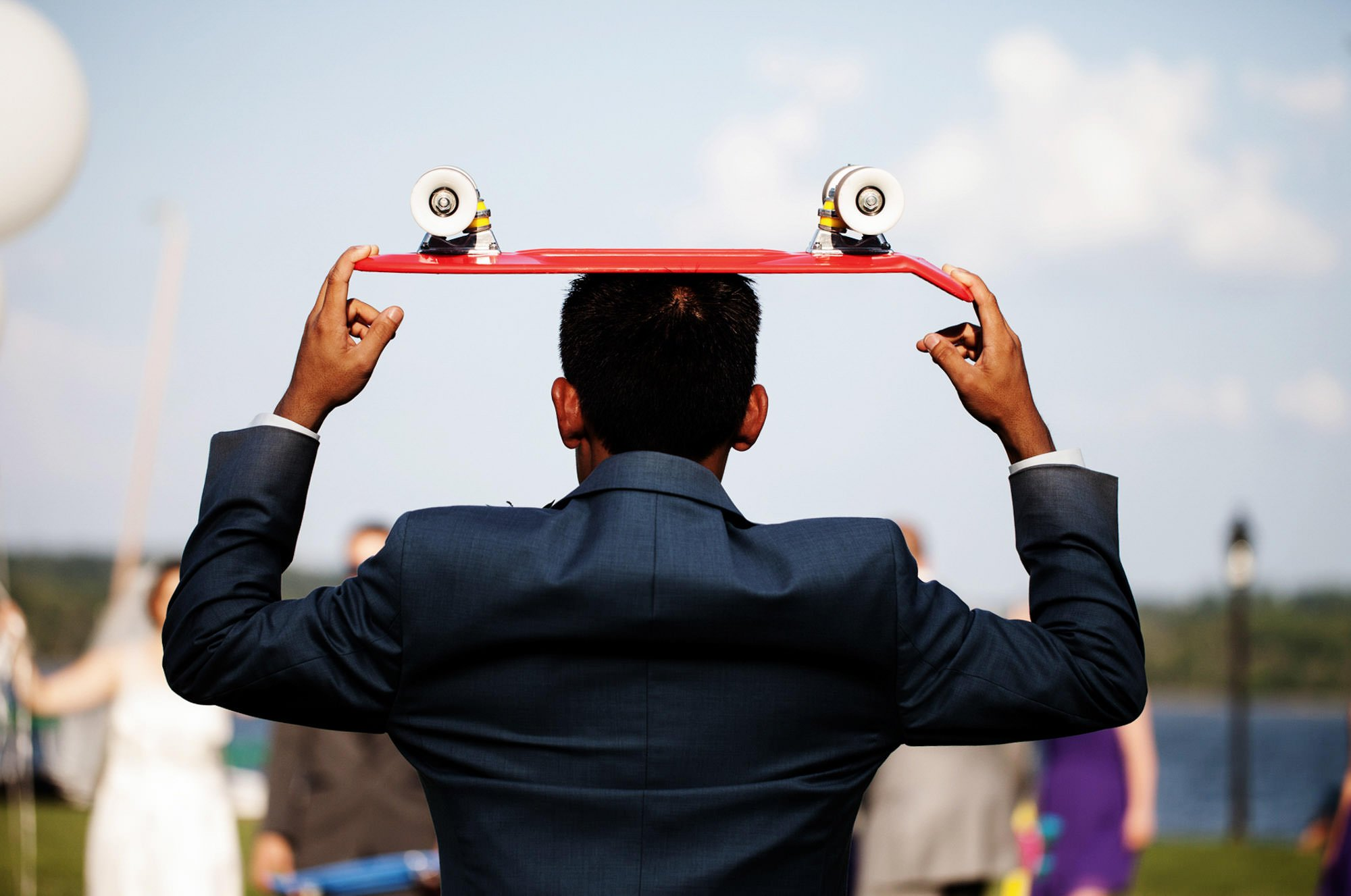 A groomsman holds a skateboard before the Topedo Factory wedding.